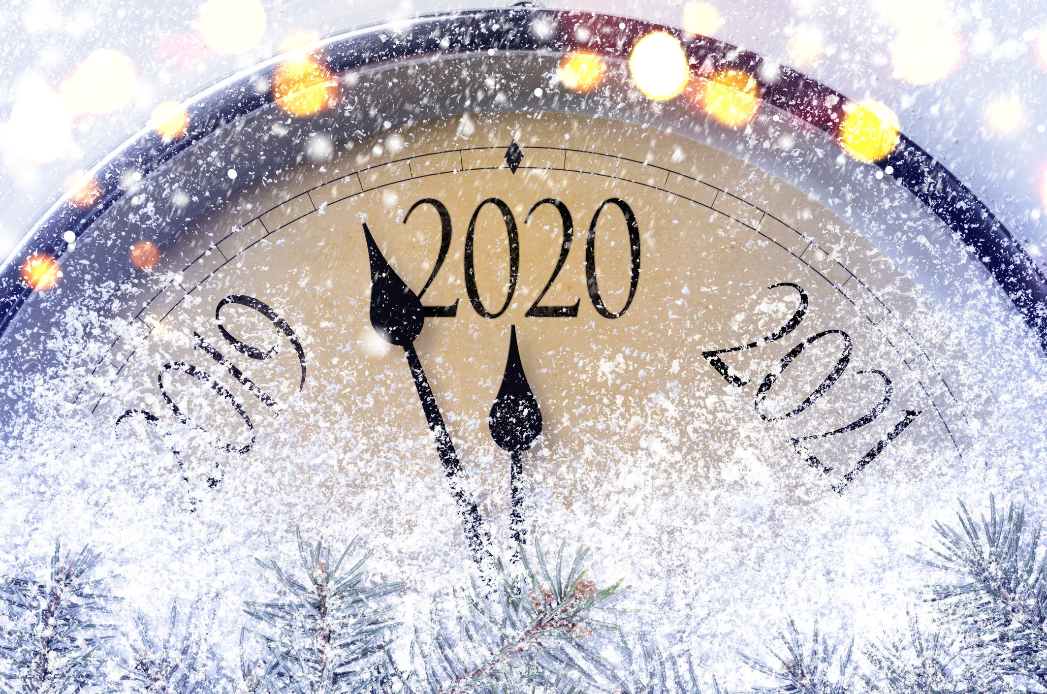 A clock covered in snow and twinkle lights switching from 2019 to 2020.
