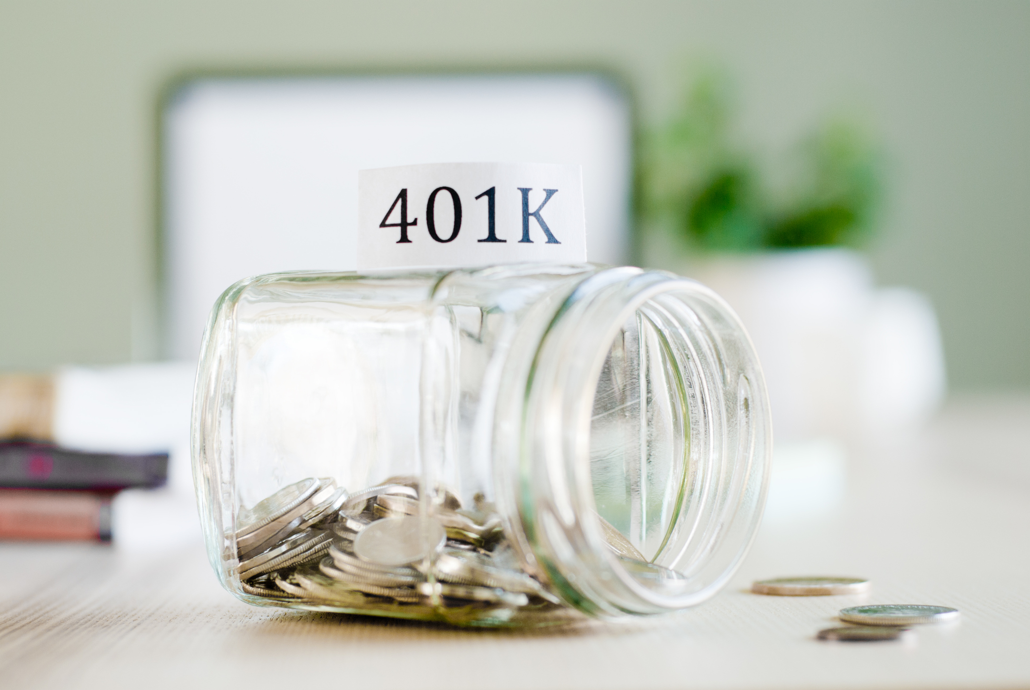 A jar filled with coins that's tipped over with the word 401(k) written on top