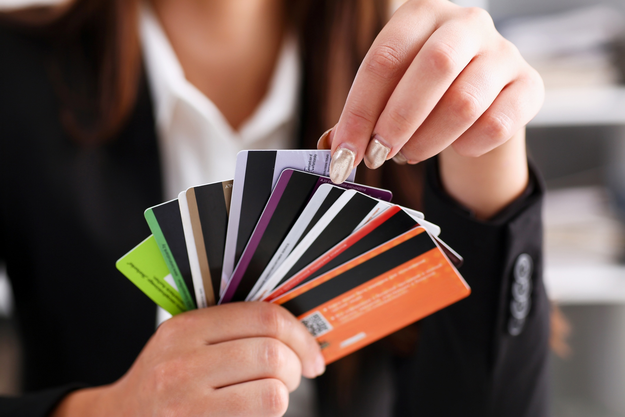 A person holding a fan of credit cards and choosing one.