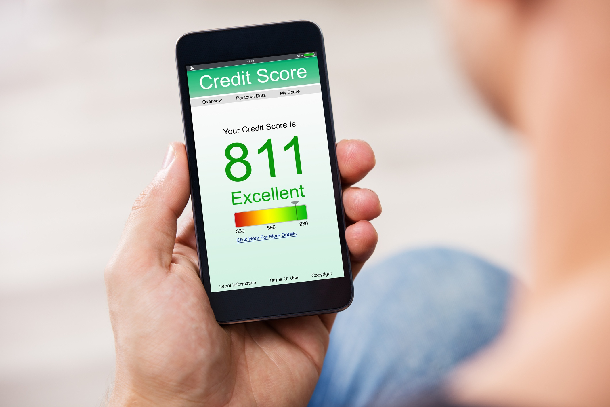 A person holding a smartphone that says 811 credit score.