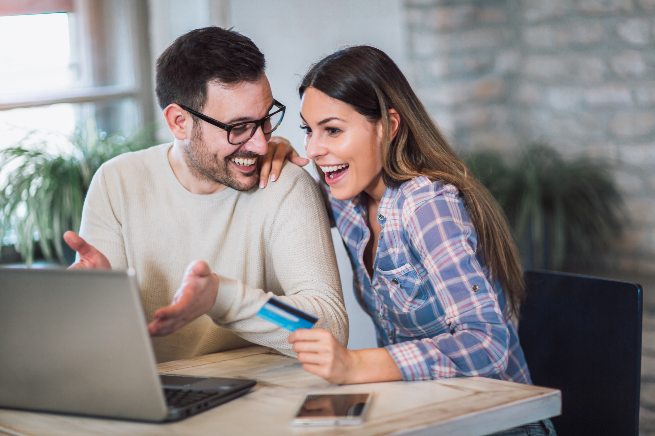 Excited Couple Looking At Good News On Laptop While Woman Holds A Credit Card