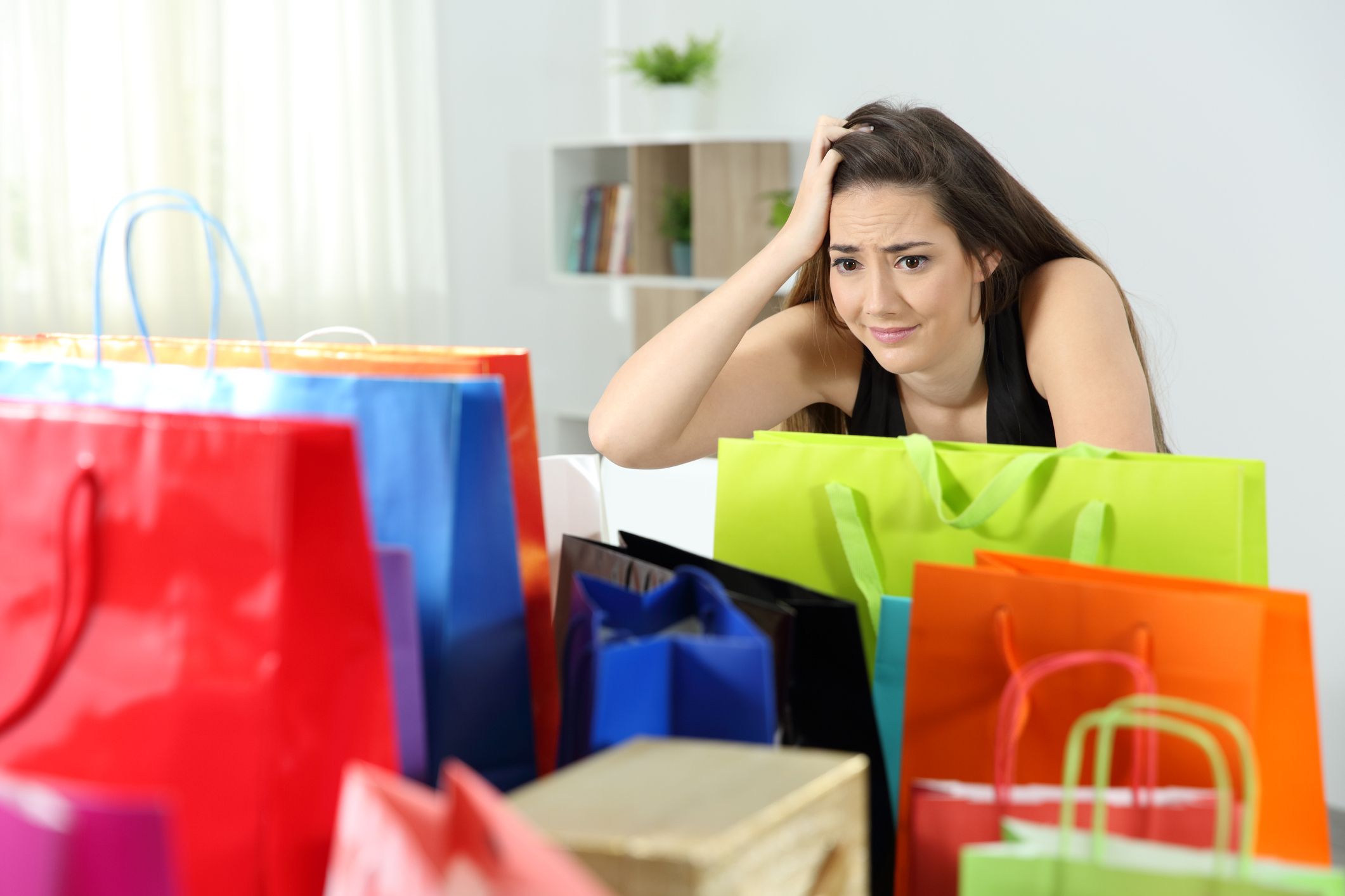 Woman in her home and freaking out as she looks at a bunch of shopping bags.