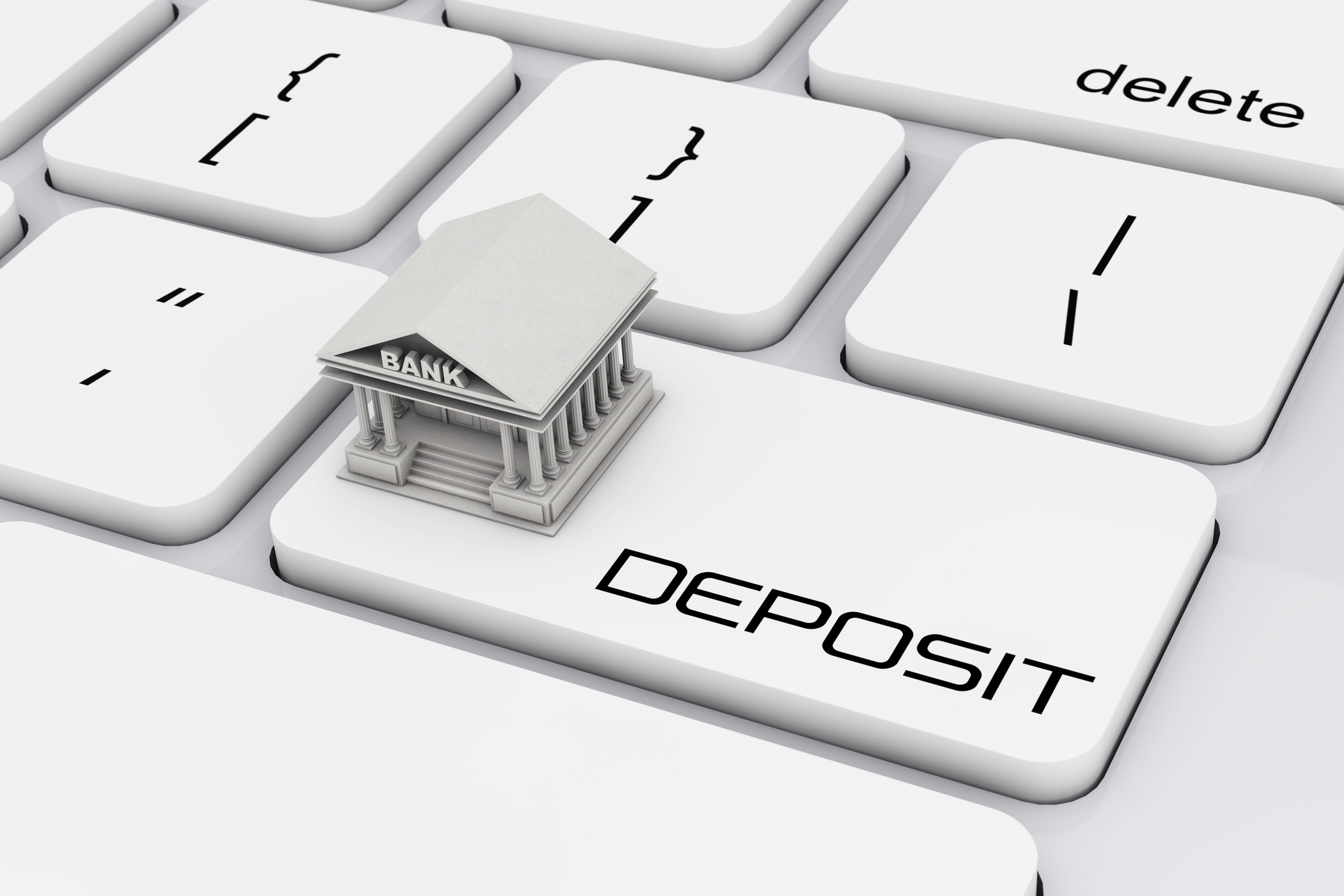 A bank figurine stands on top of a keyboard, on a key labeled deposit.