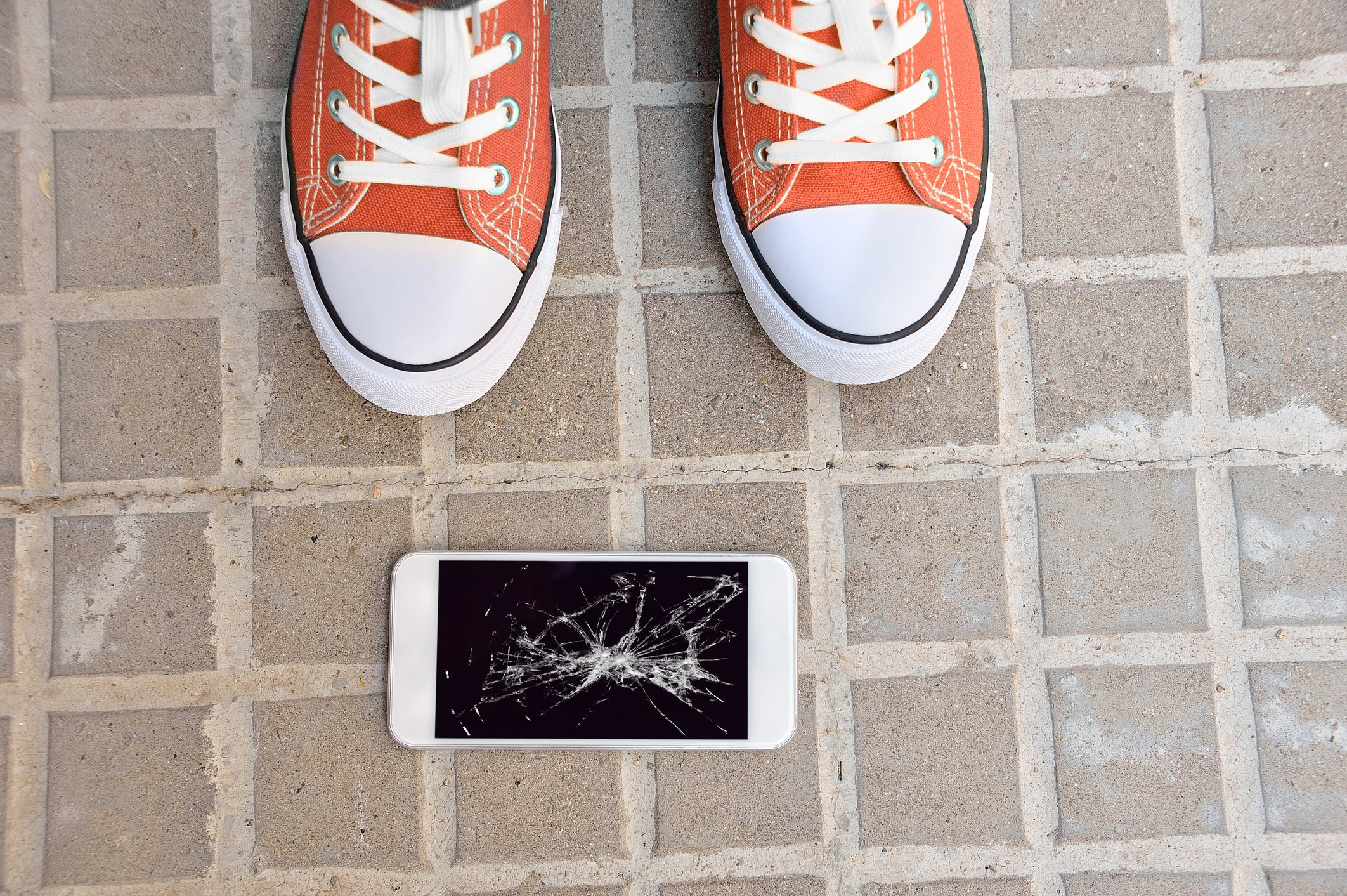 Someone standing next to a dropped cell phone with a broken screen.