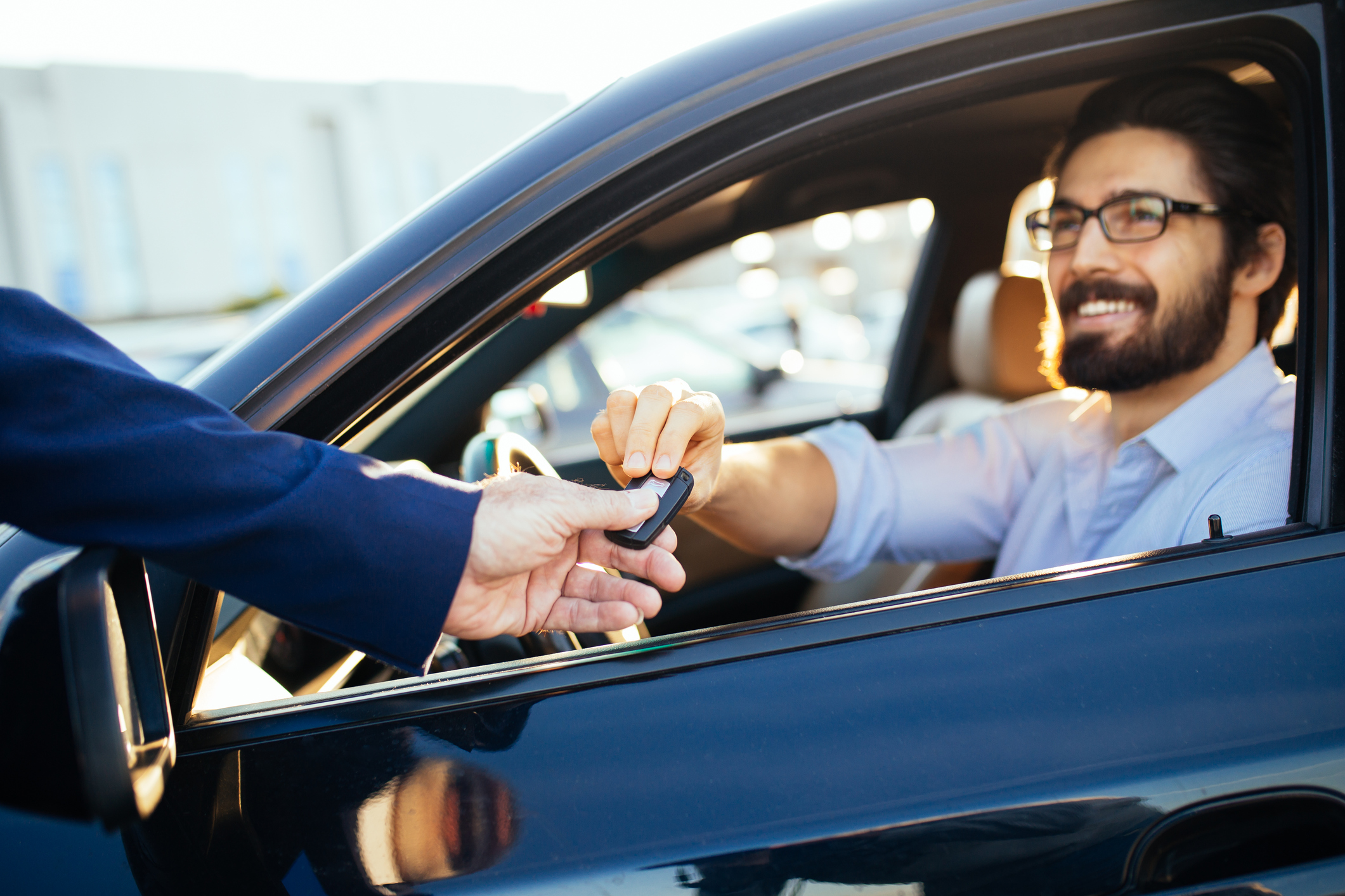 Man in suit jacket handing car keys to man sitting in vehicle.