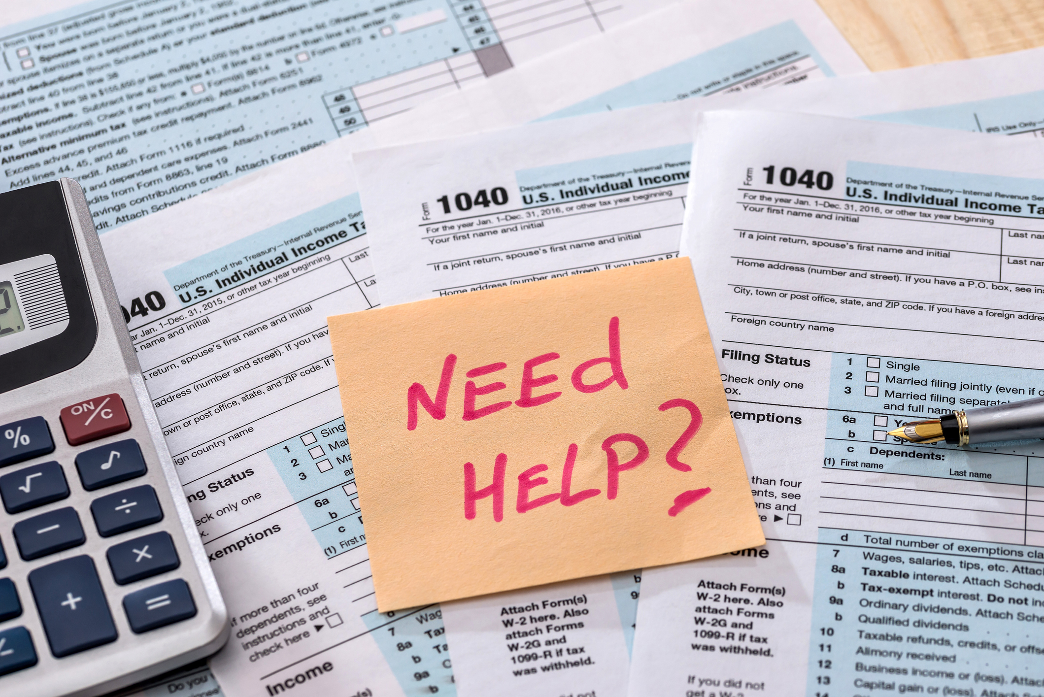 Stack of tax forms with post-it note reading Need Help? on top.