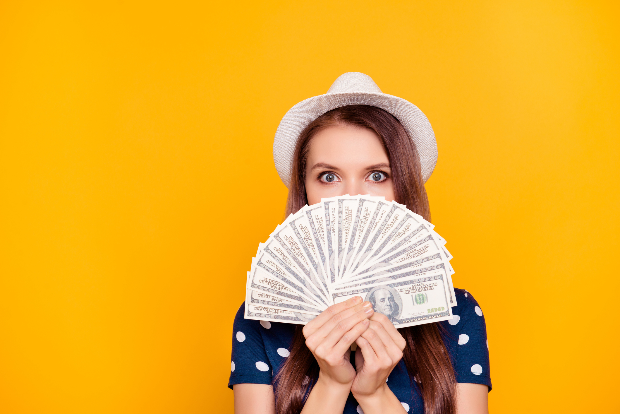 A young woman wearing a hat holds a fan of hundred dollar bills.