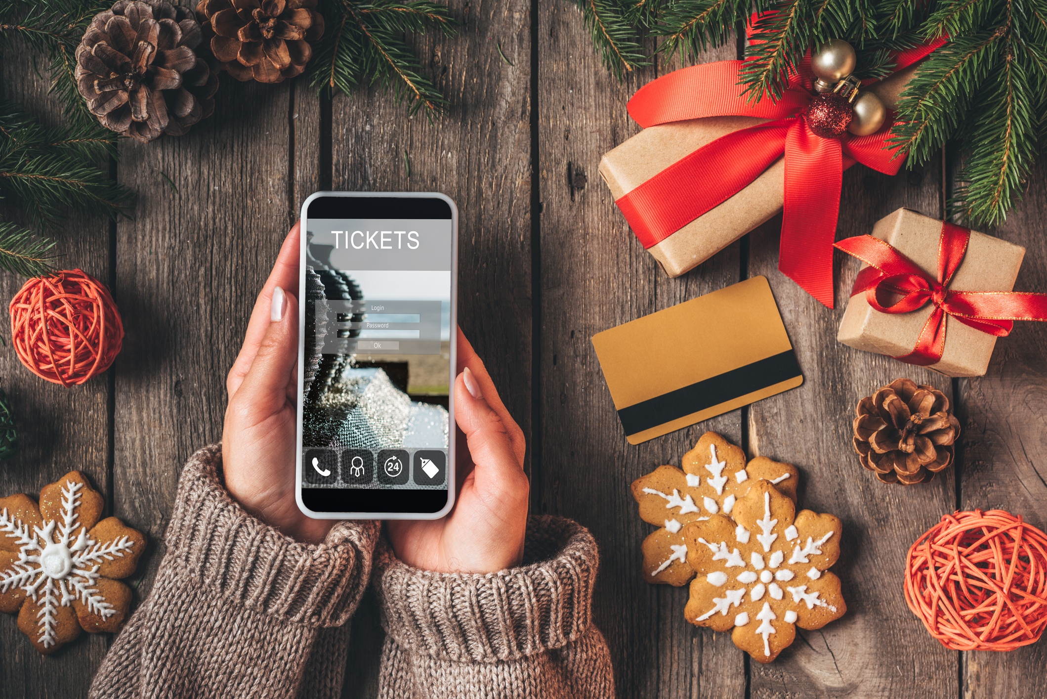 Christmas decor and a credit card on a table around hands holding a phone showing a ticket purchase screen.