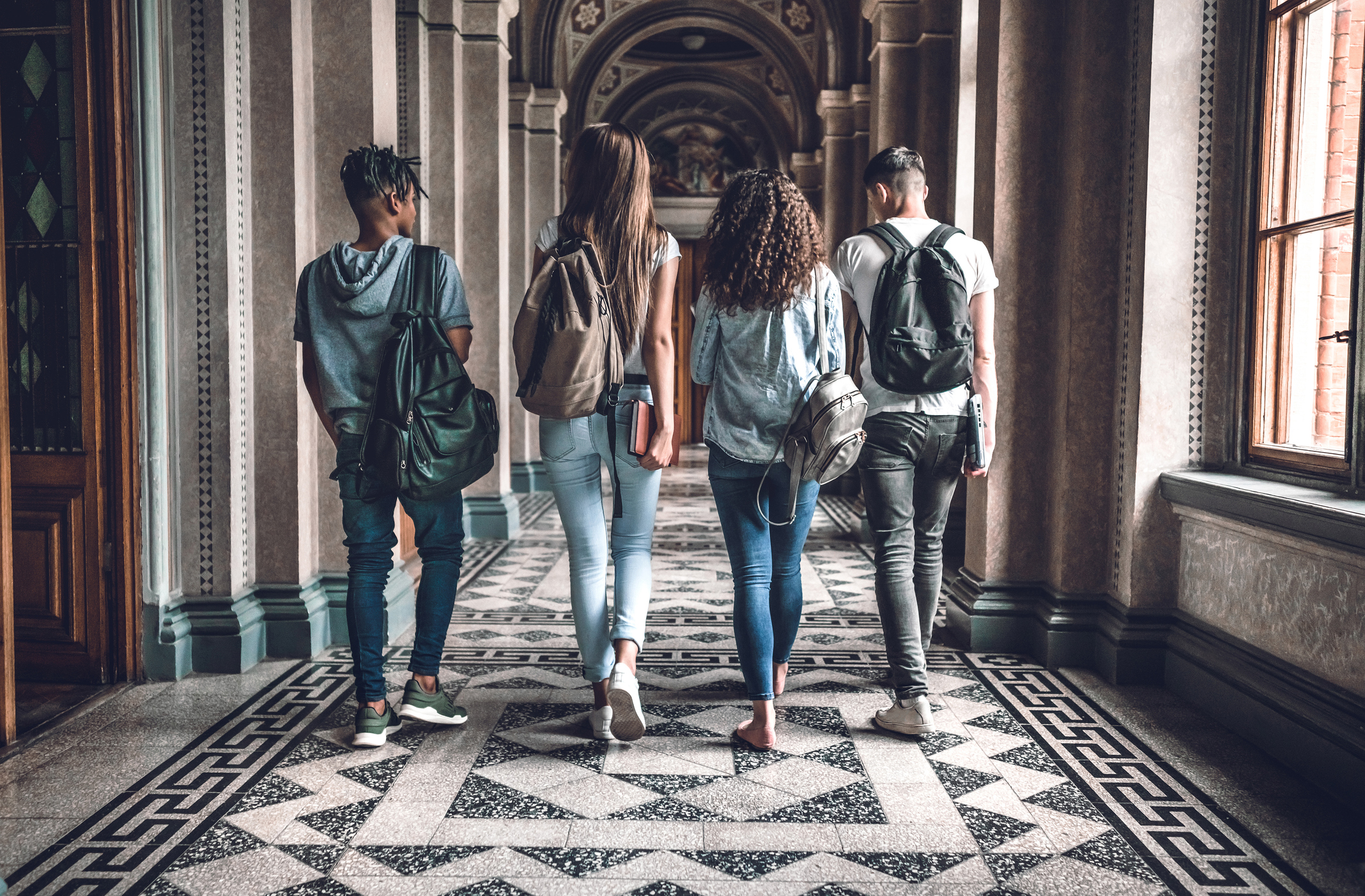 College students walking in an arched hallway.