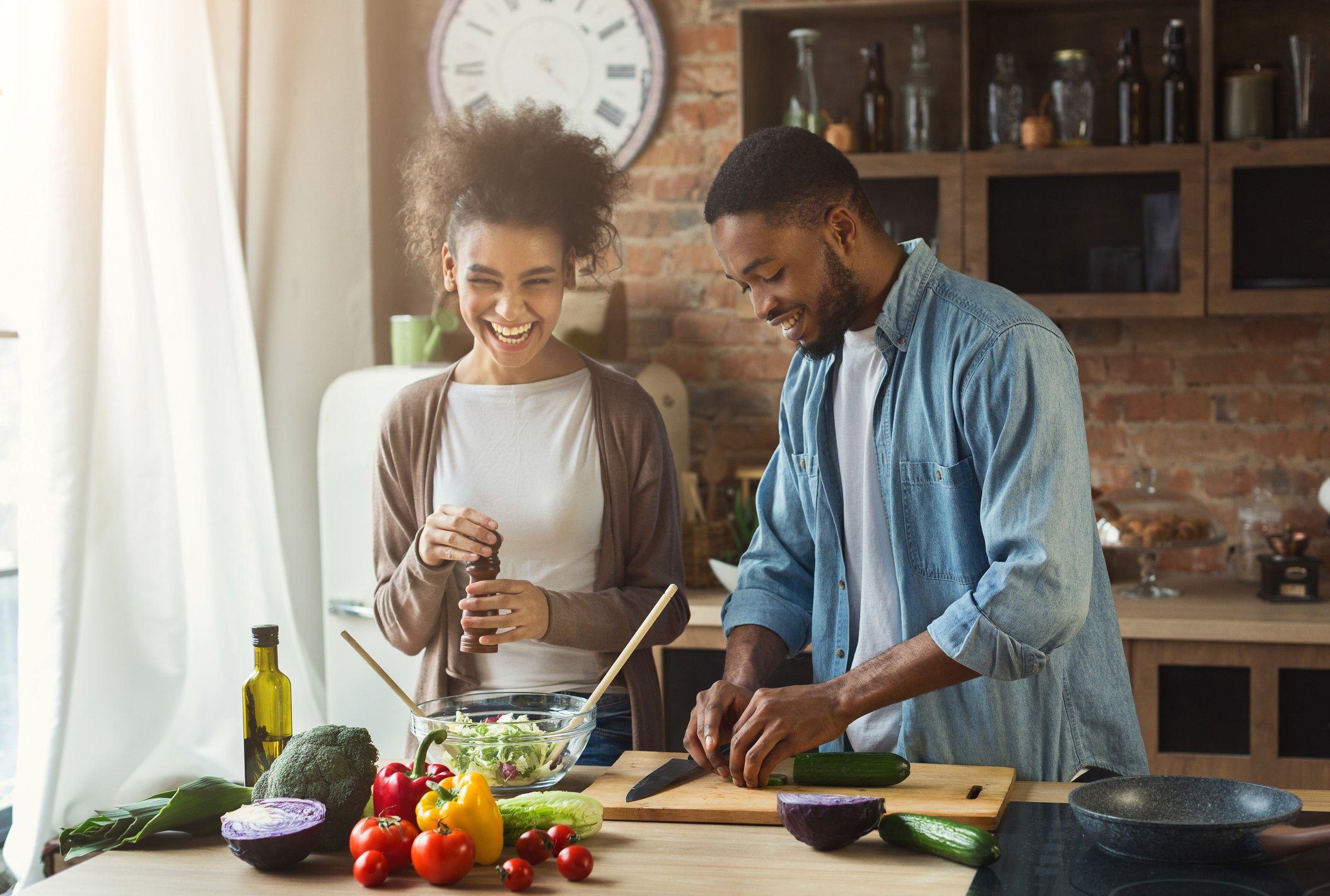 A happy young couple cooking at home.