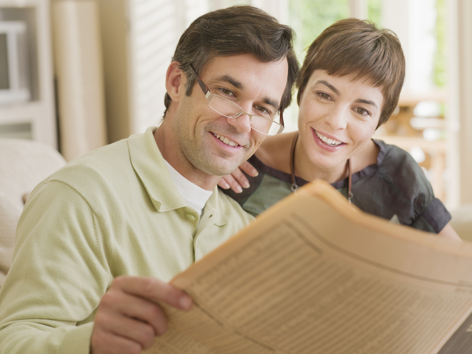 A couple looking at a newspaper together.