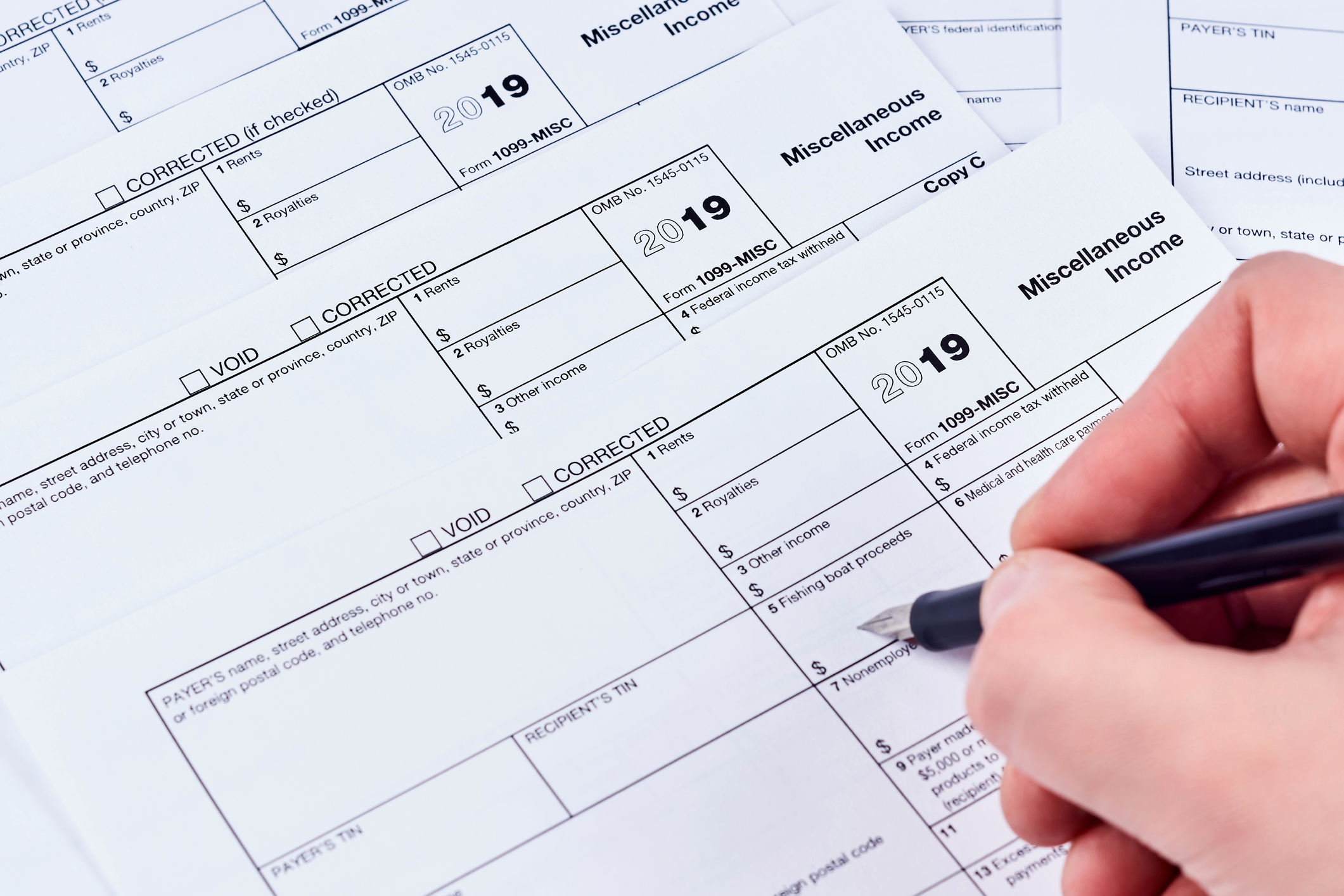 Person filling out a miscellaneous income tax form.