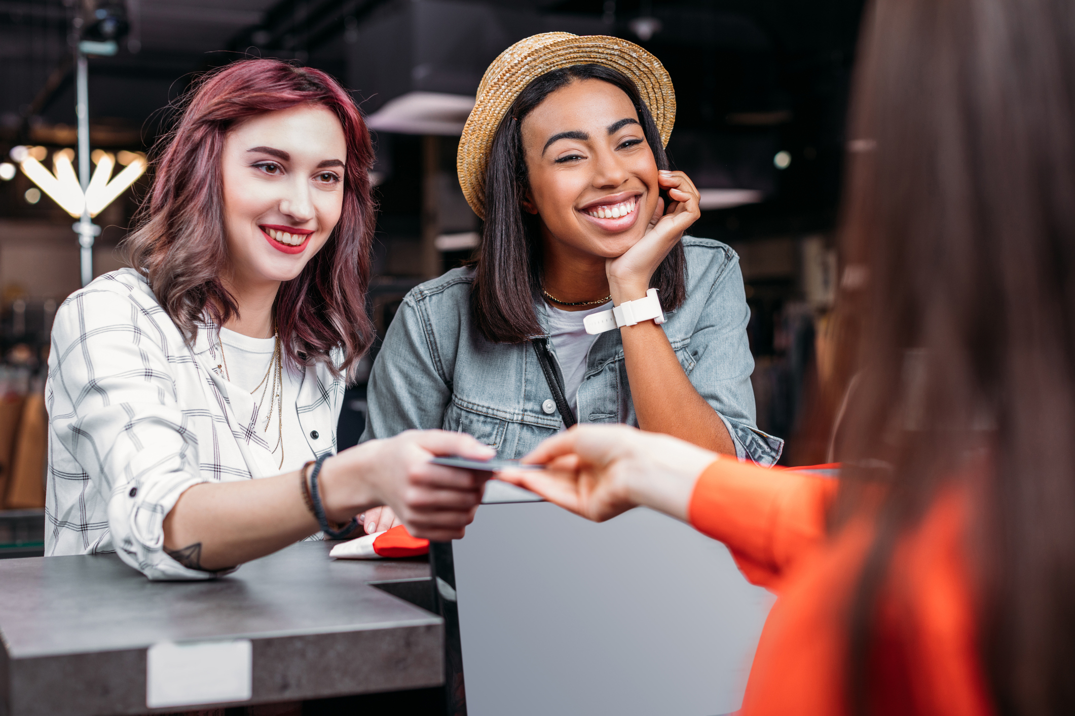 Two young women interact with cashier as one hands over a credit card.