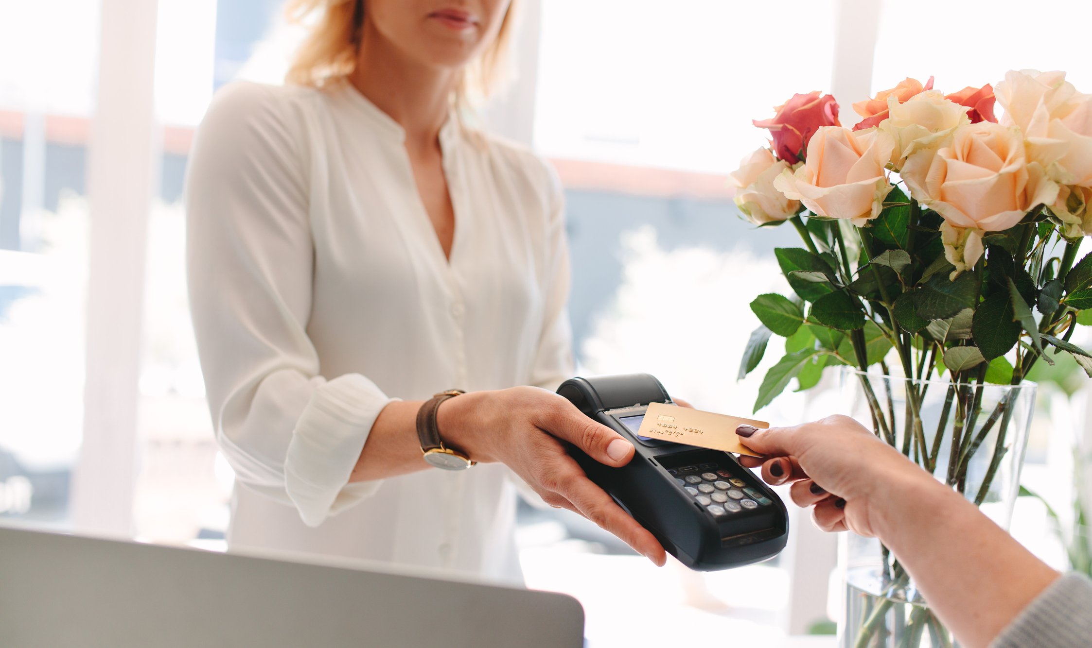 Someone paying on a credit card reader with flowers in the background.