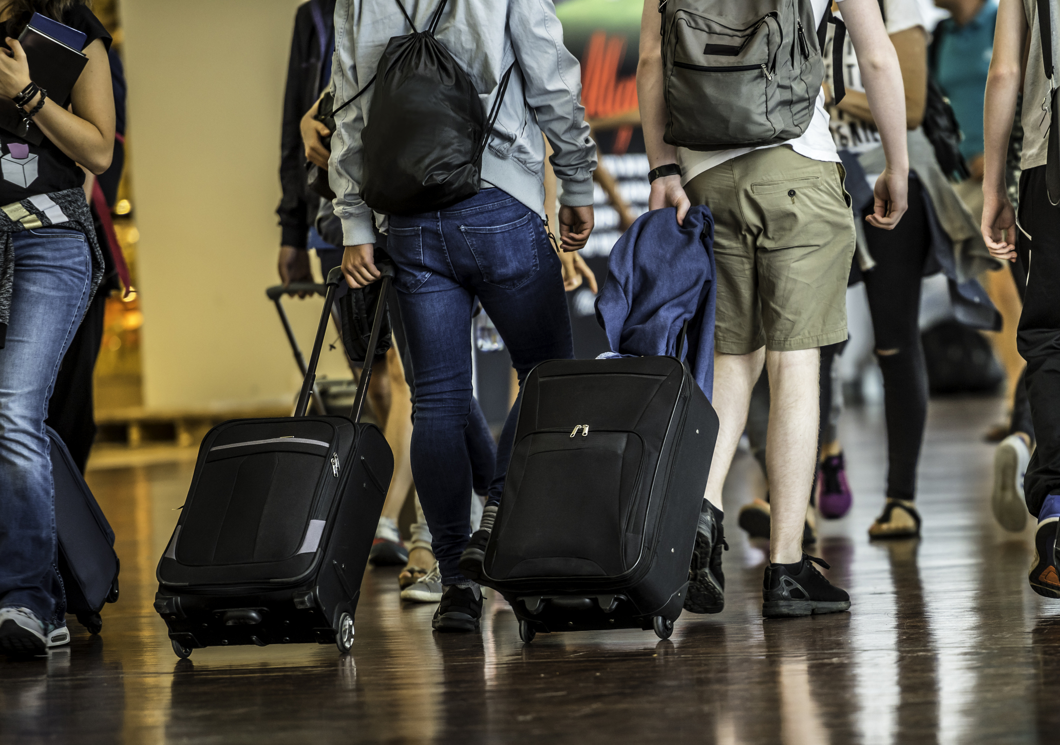 Travelers with suitcases walking through a crowded airport terminal.
