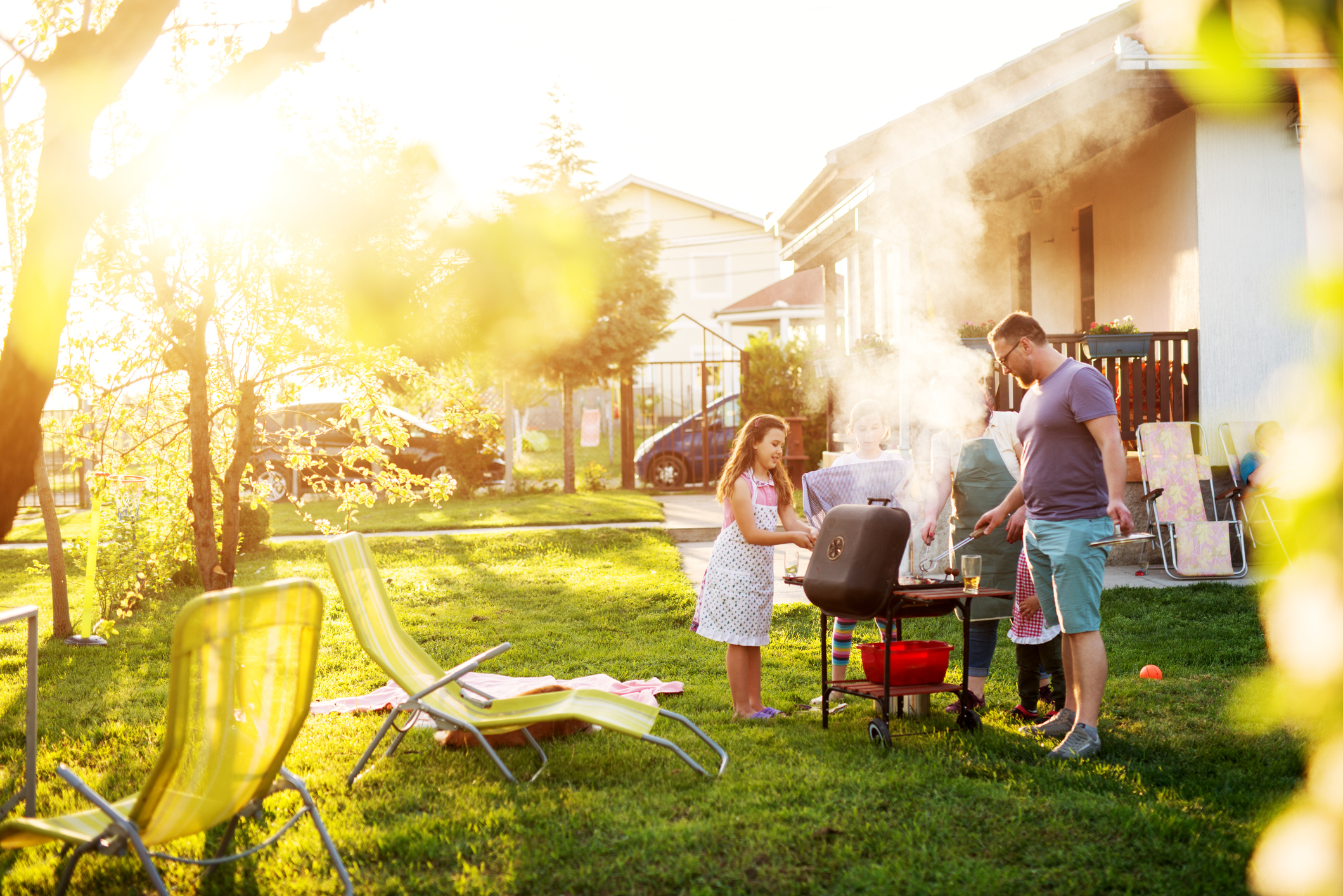 A family barbecuing in a sunny backyard.