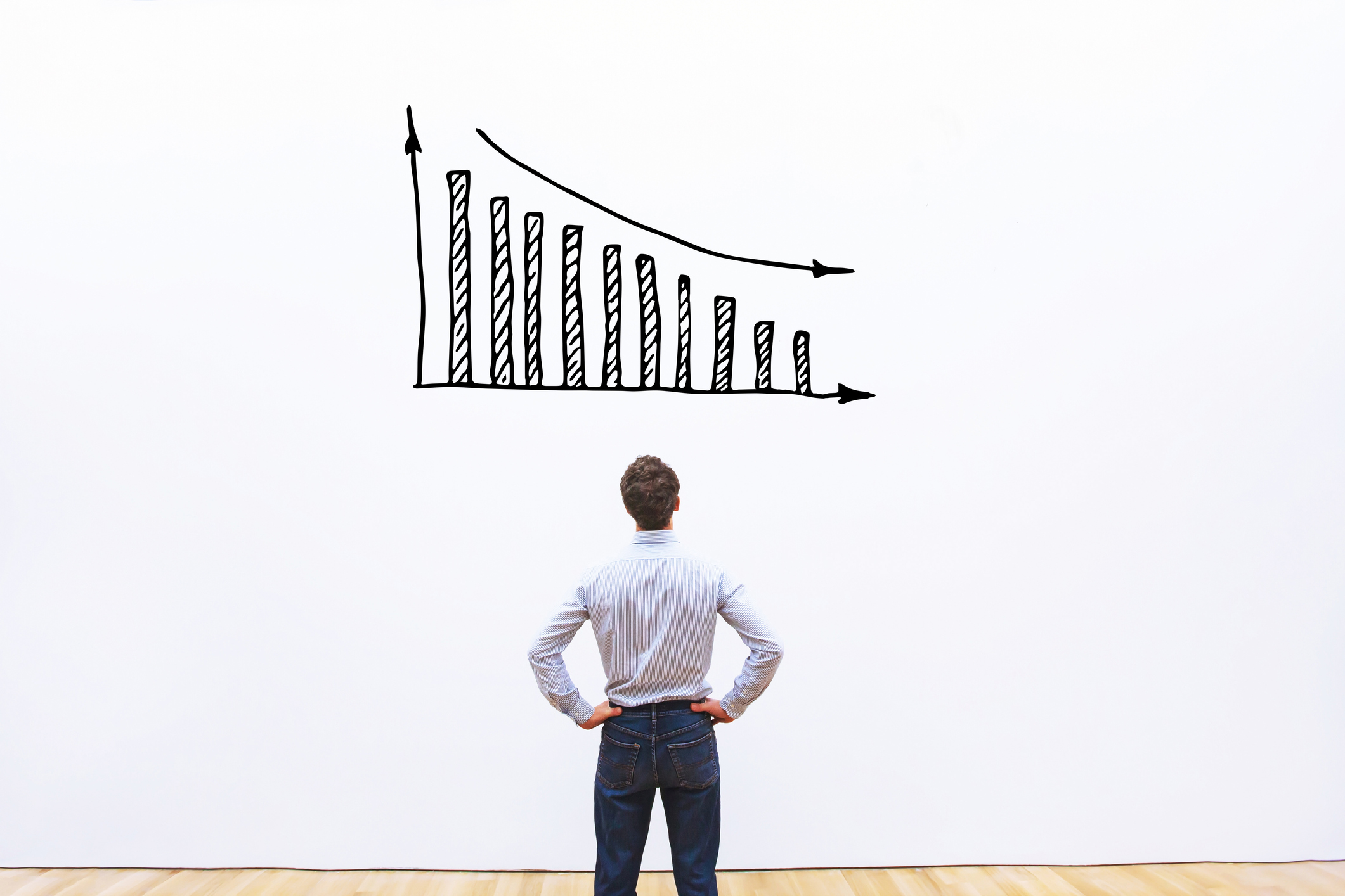 Man standing in front of a white board with a decreasing bar graph drawn on it