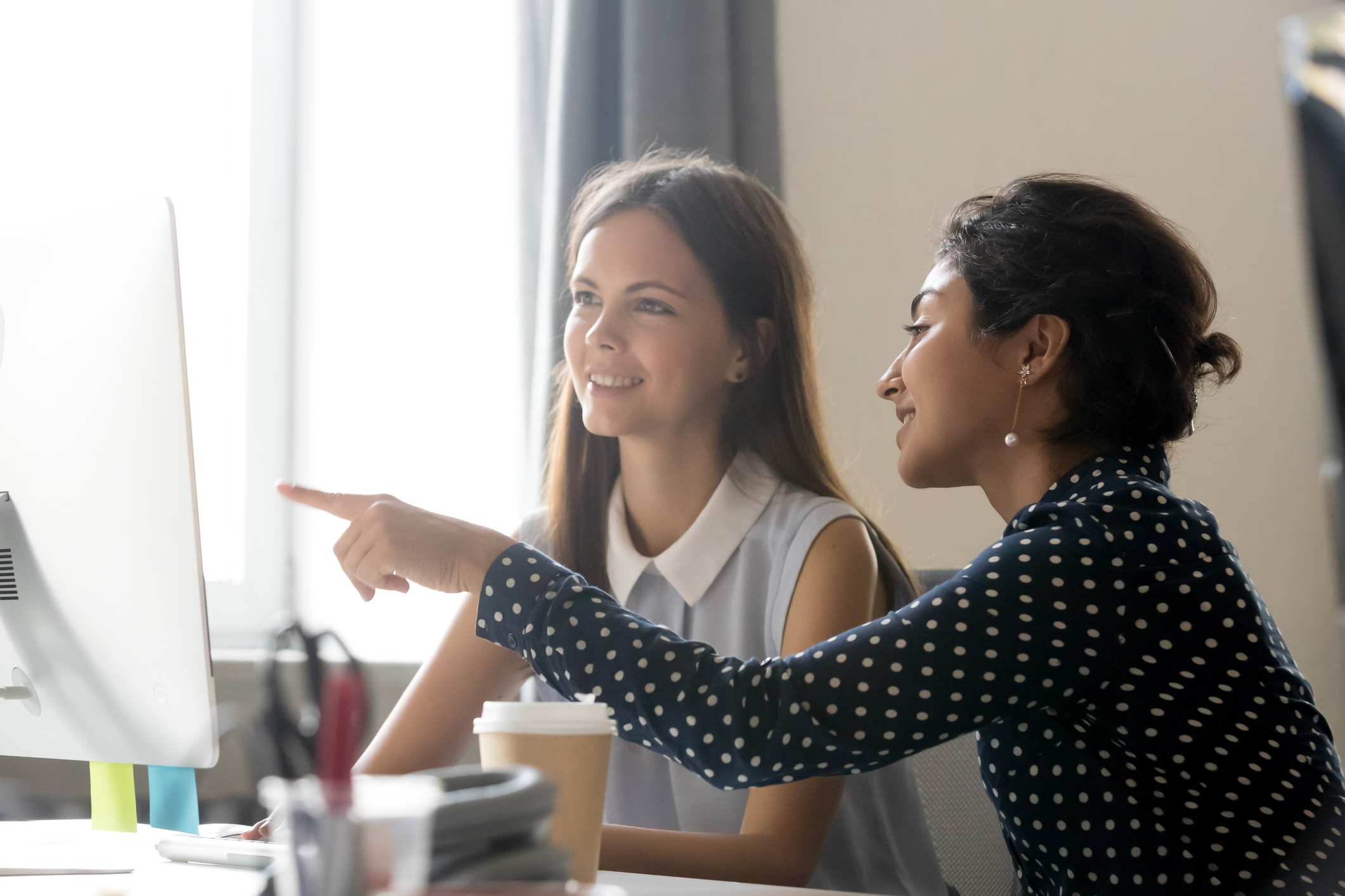 A woman mentoring a younger woman and pointing at computer.
