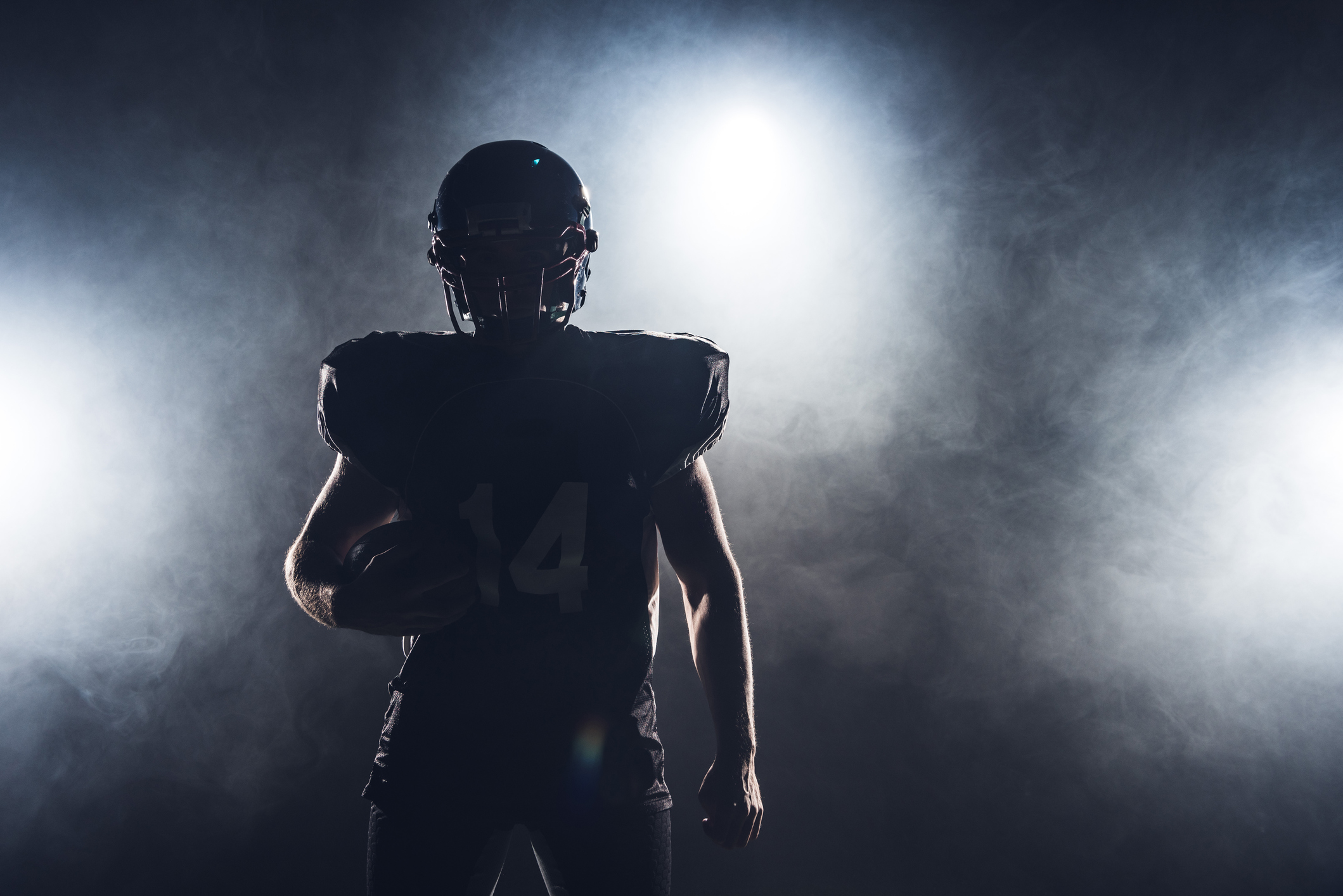 The silhouette of a football player in pads and a helmet holding a football.