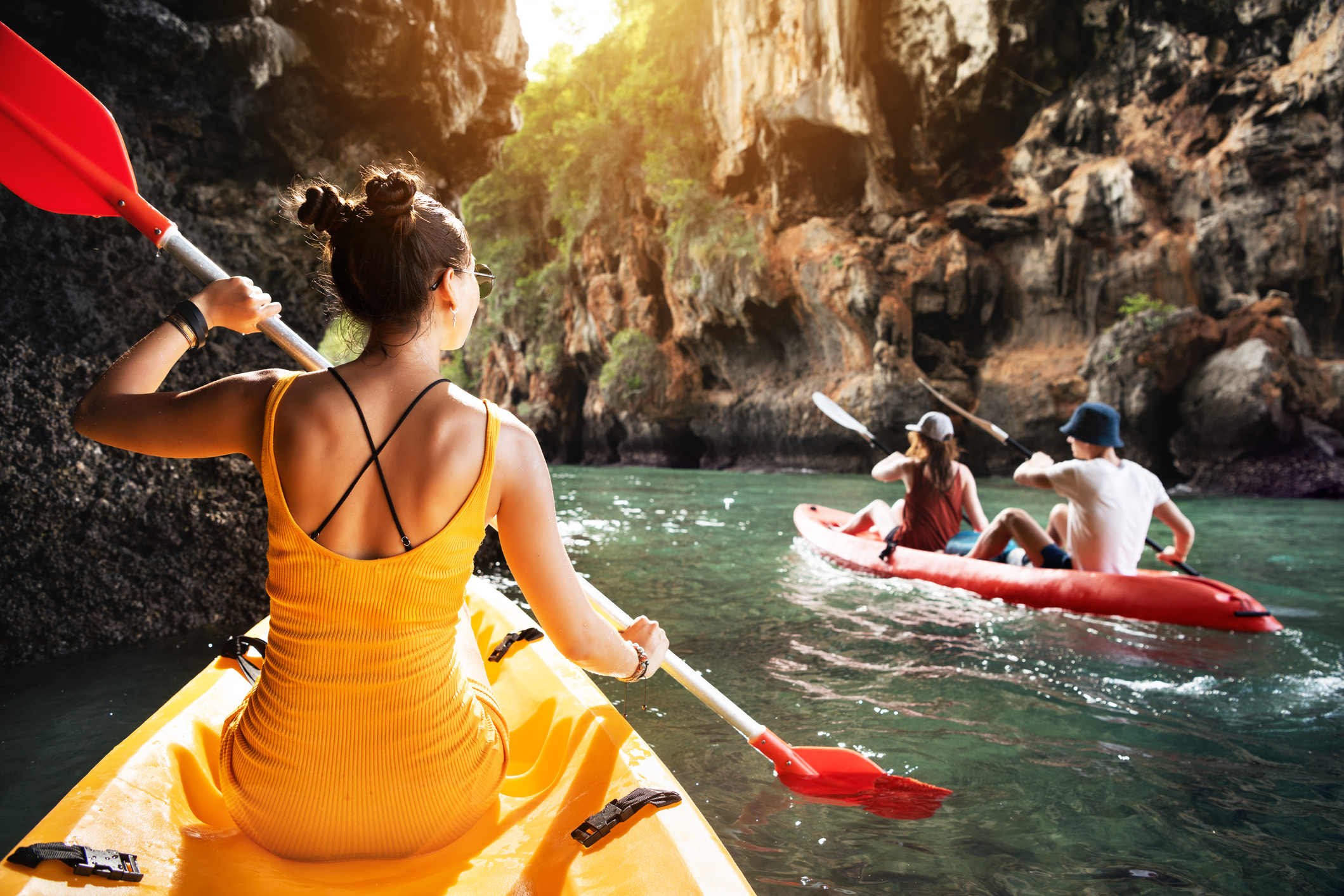 Three people kayaking in a tropical canyon.
