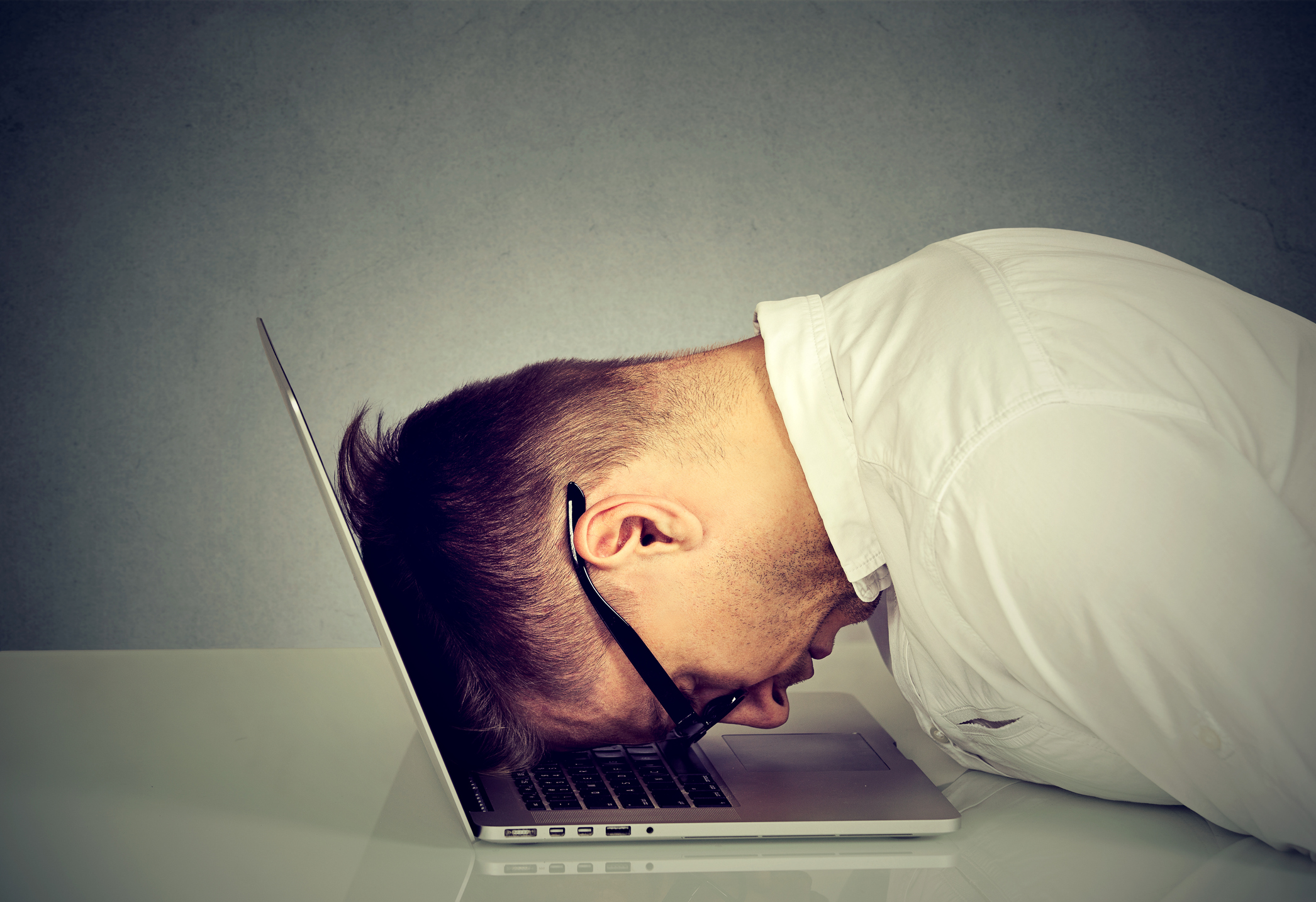Frustrated man with head resting on a laptop