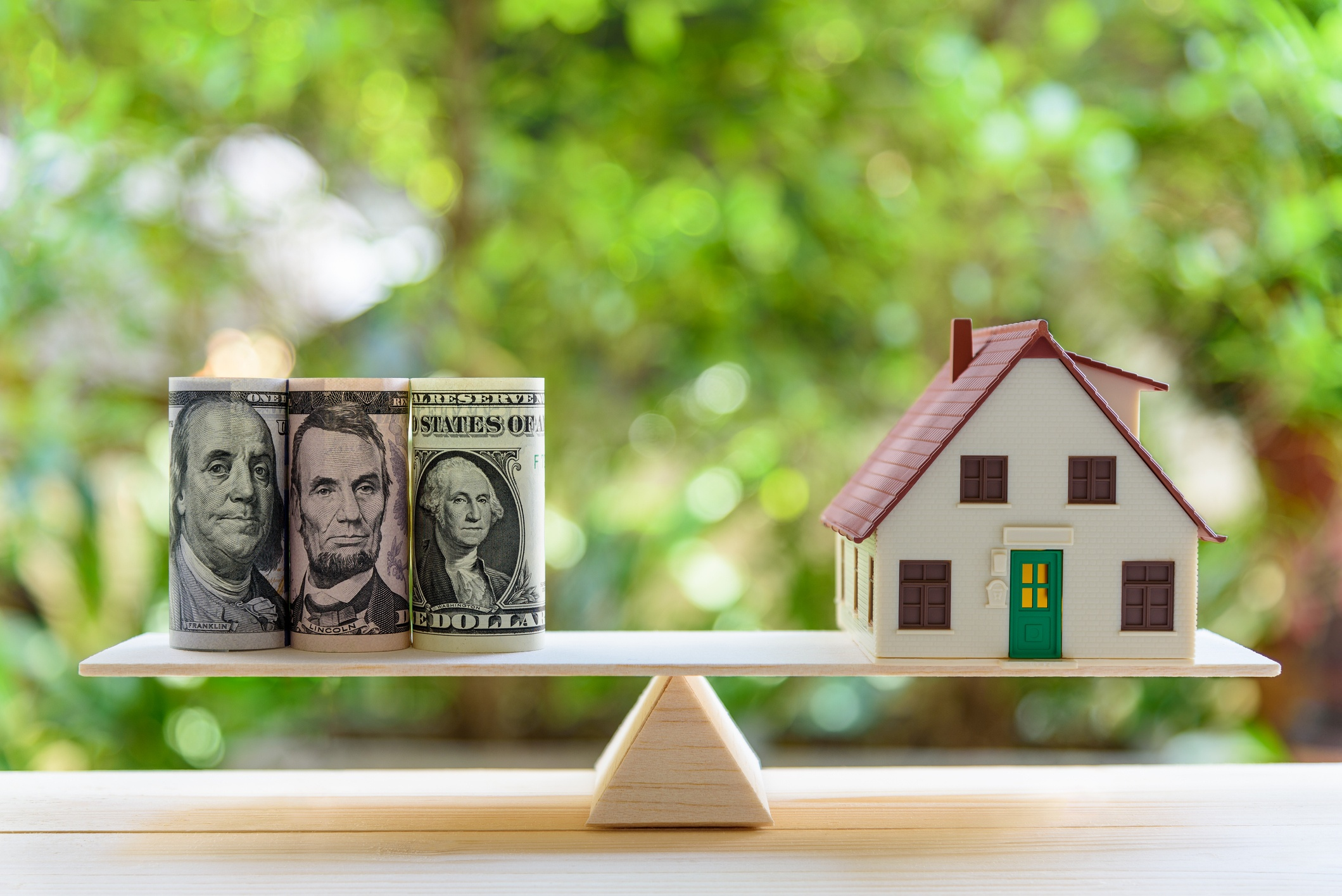 House and money on a balance