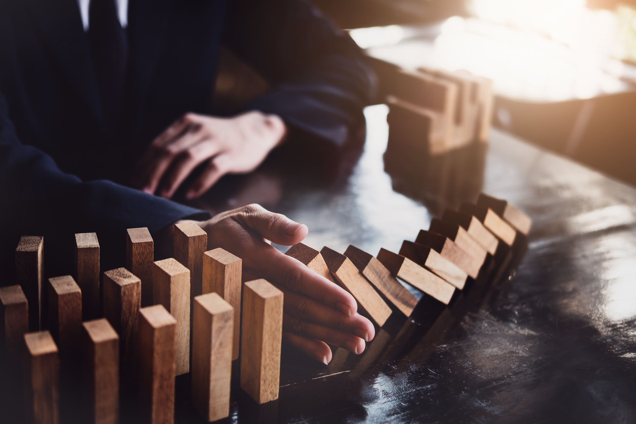 A man's hand stops a row of wooden dominoes from falling over.