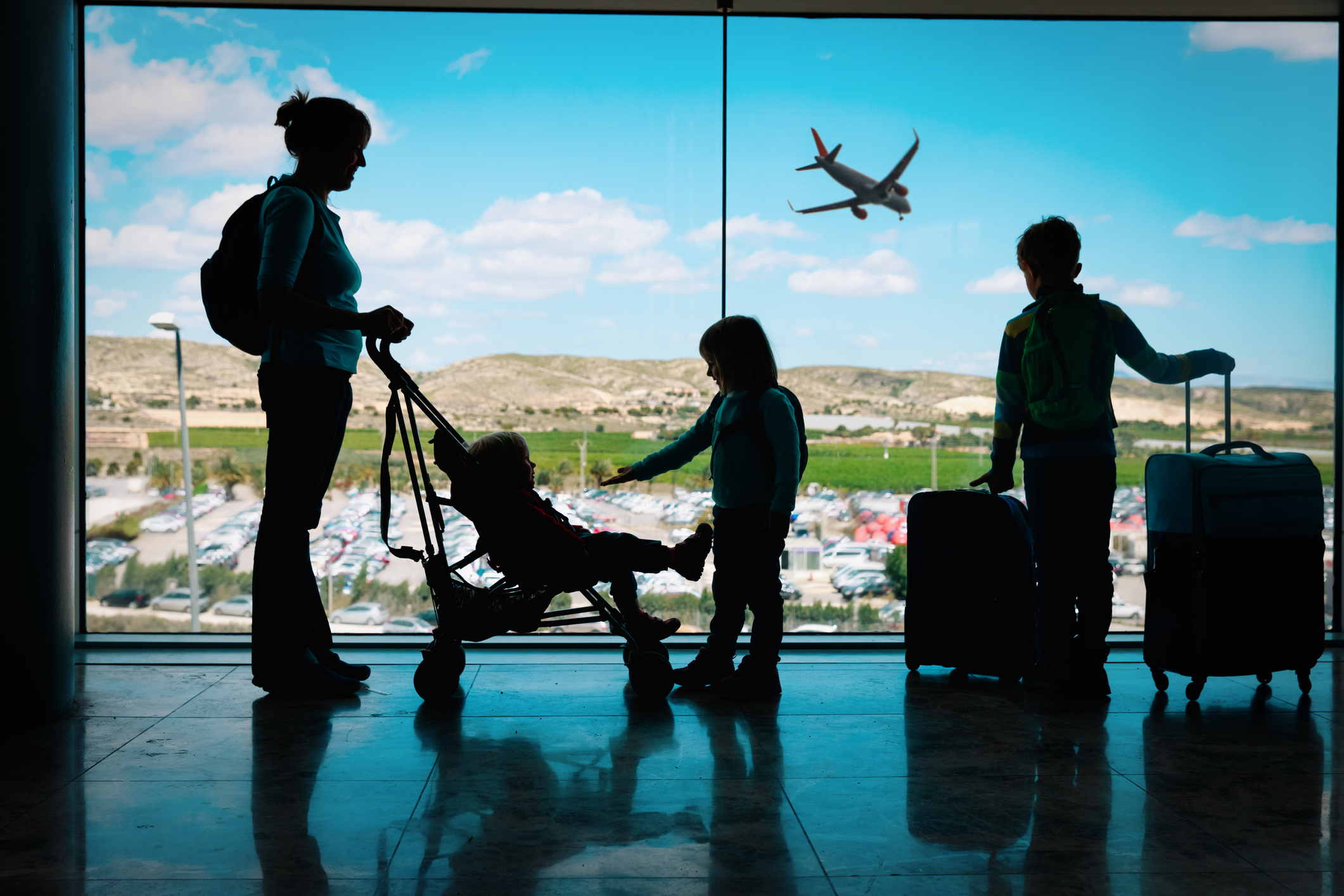 Mother with three children and luggage silhouetted in airport.