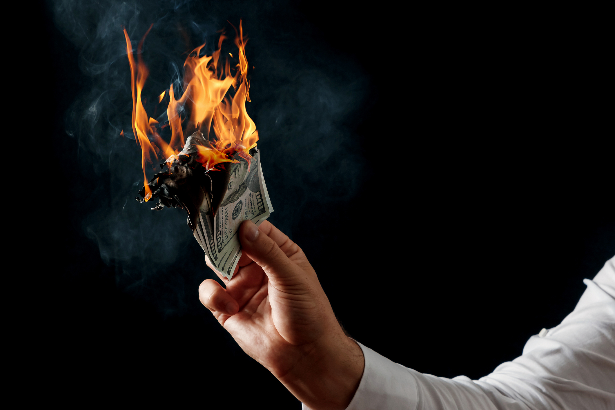 Hand holding a wad of 100-dollar bills set ablaze.