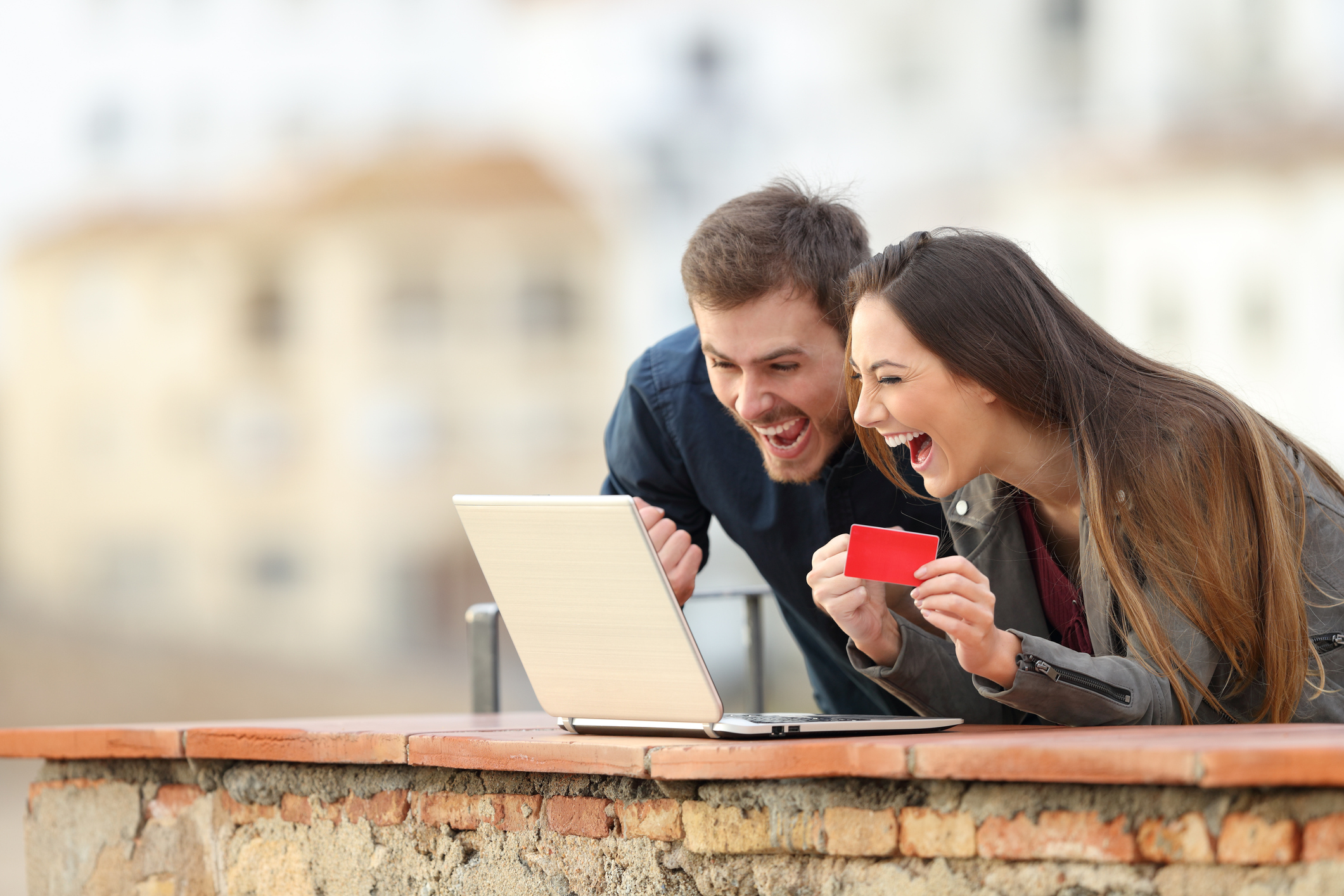 Young couple very excited about their credit card and what's on their computer screen.