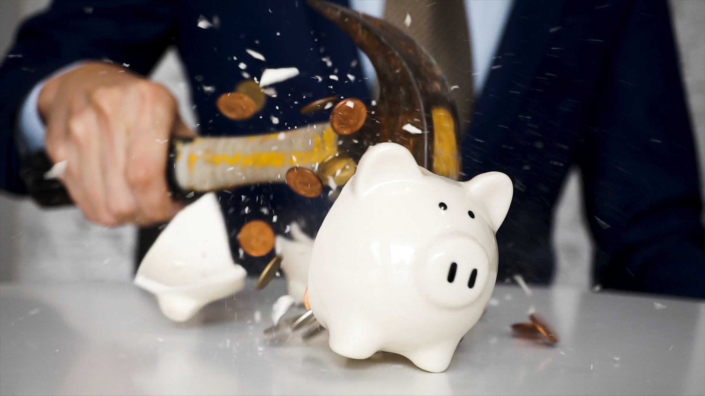 Man in suit shattering piggy bank with hammer.