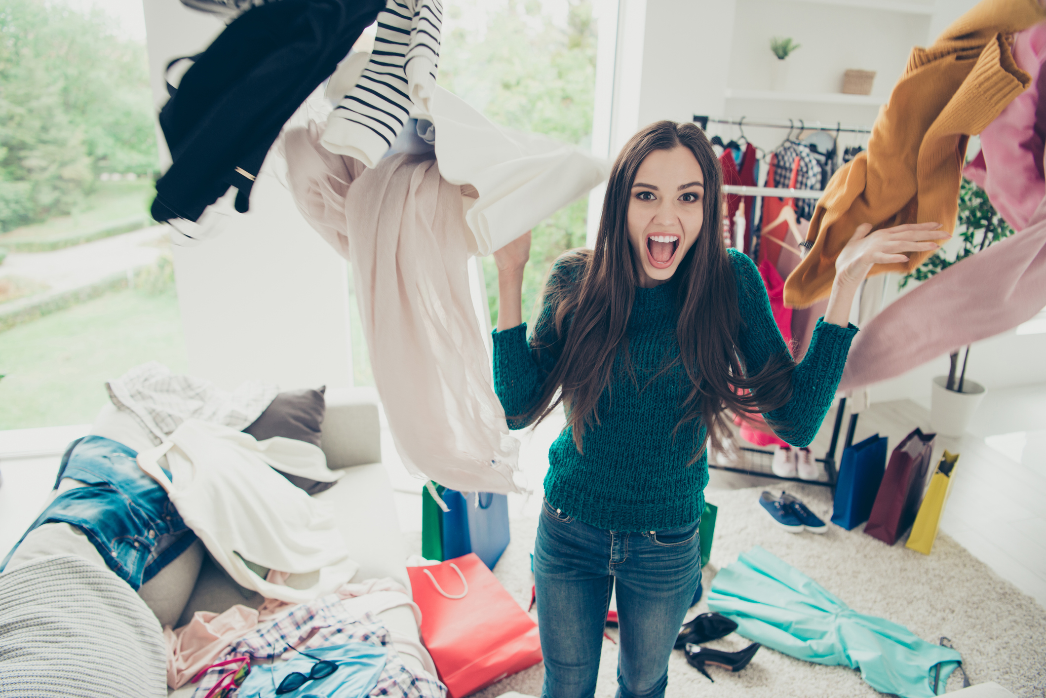 Young woman shrieking as she tosses a bunch of clothes into the air.