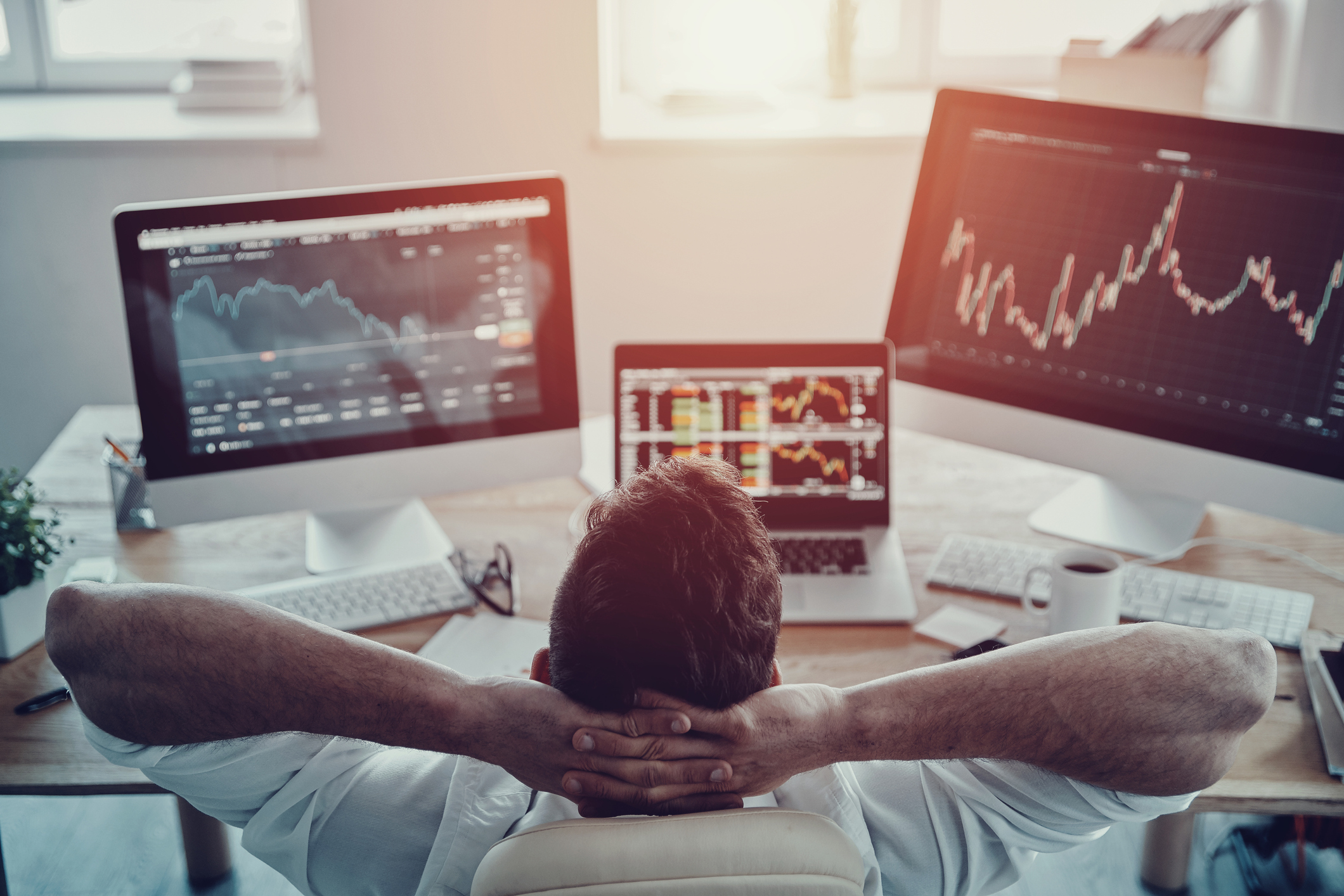Guy leaning back and monitoring three screens featuring various stock information.