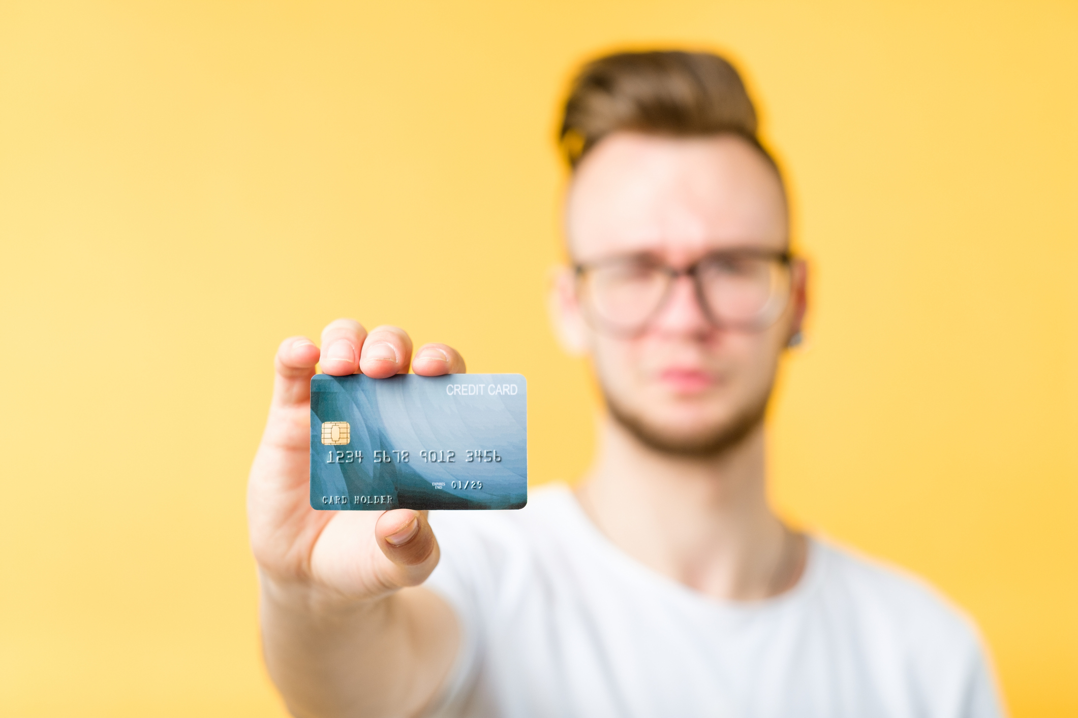 Out-of-focus bespectacled young man with punk hairstyle presenting credit card.
