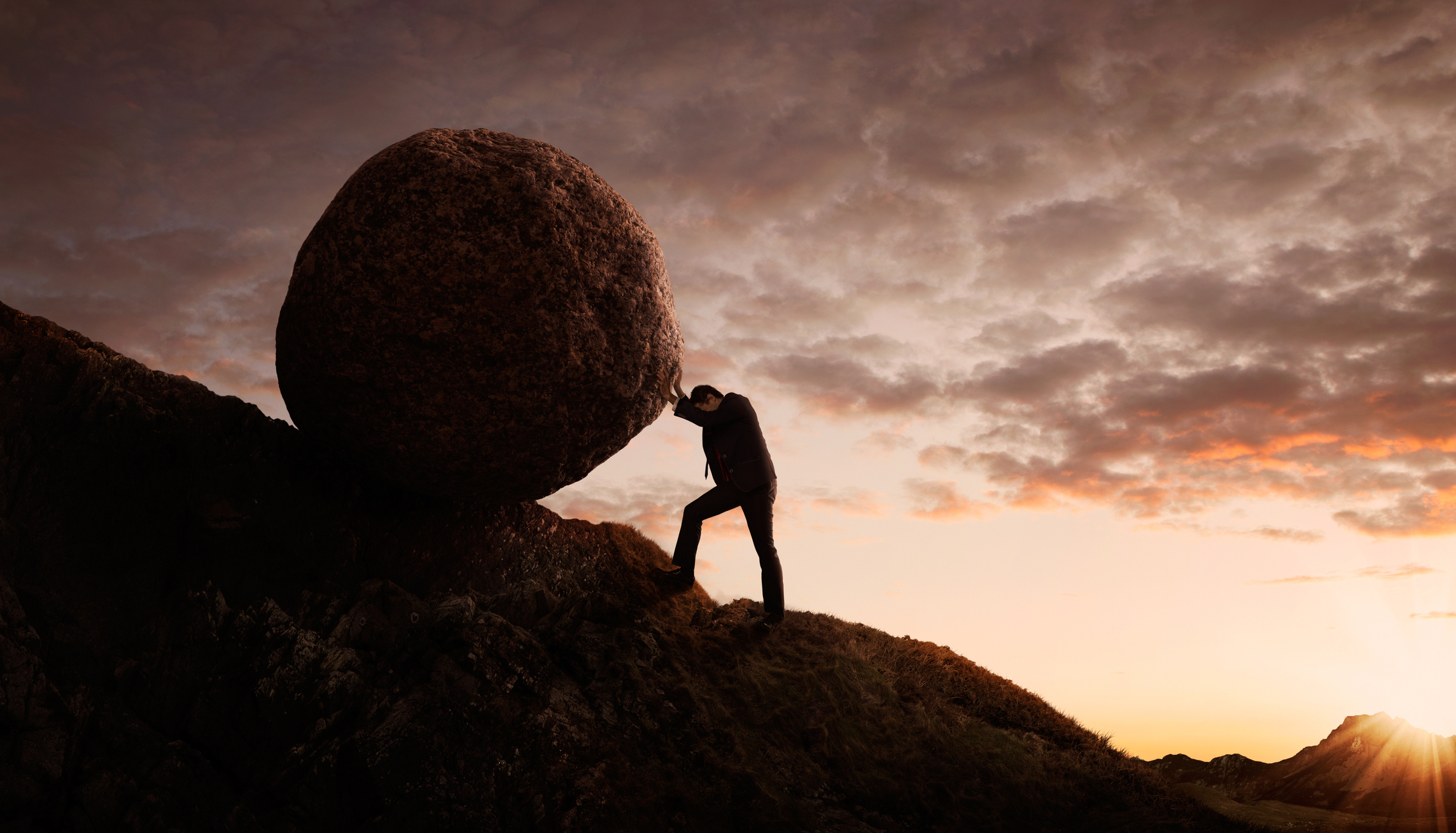 Man in suit rolling boulder uphill against wild sunset backdrop.