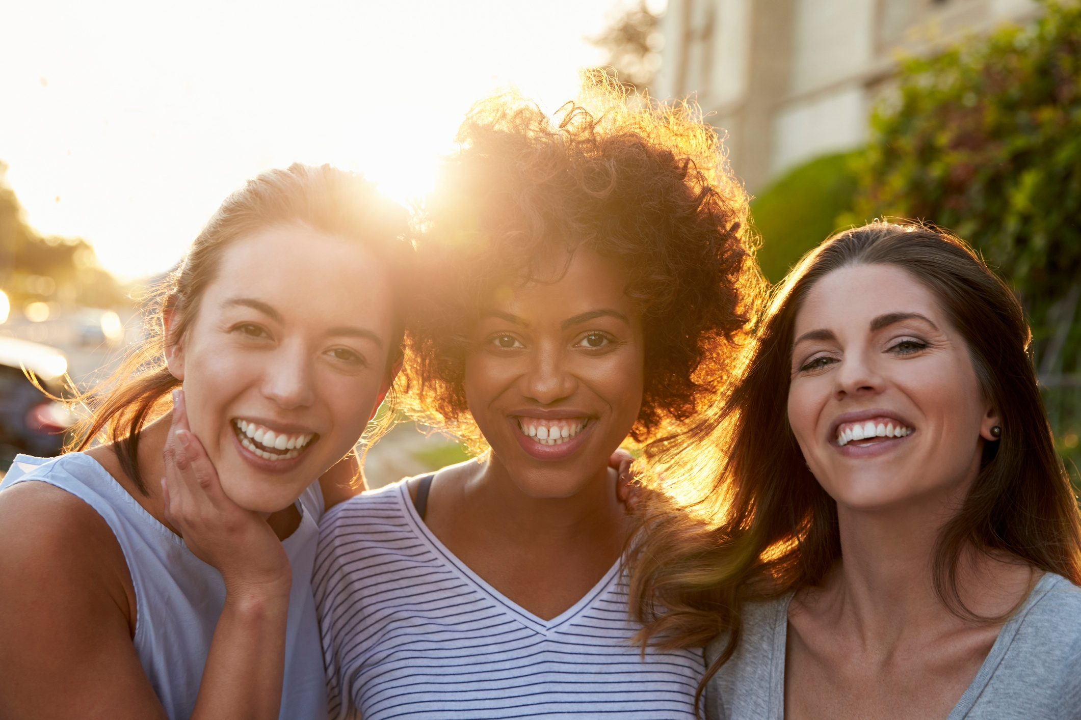 Three smiling women in their 30s