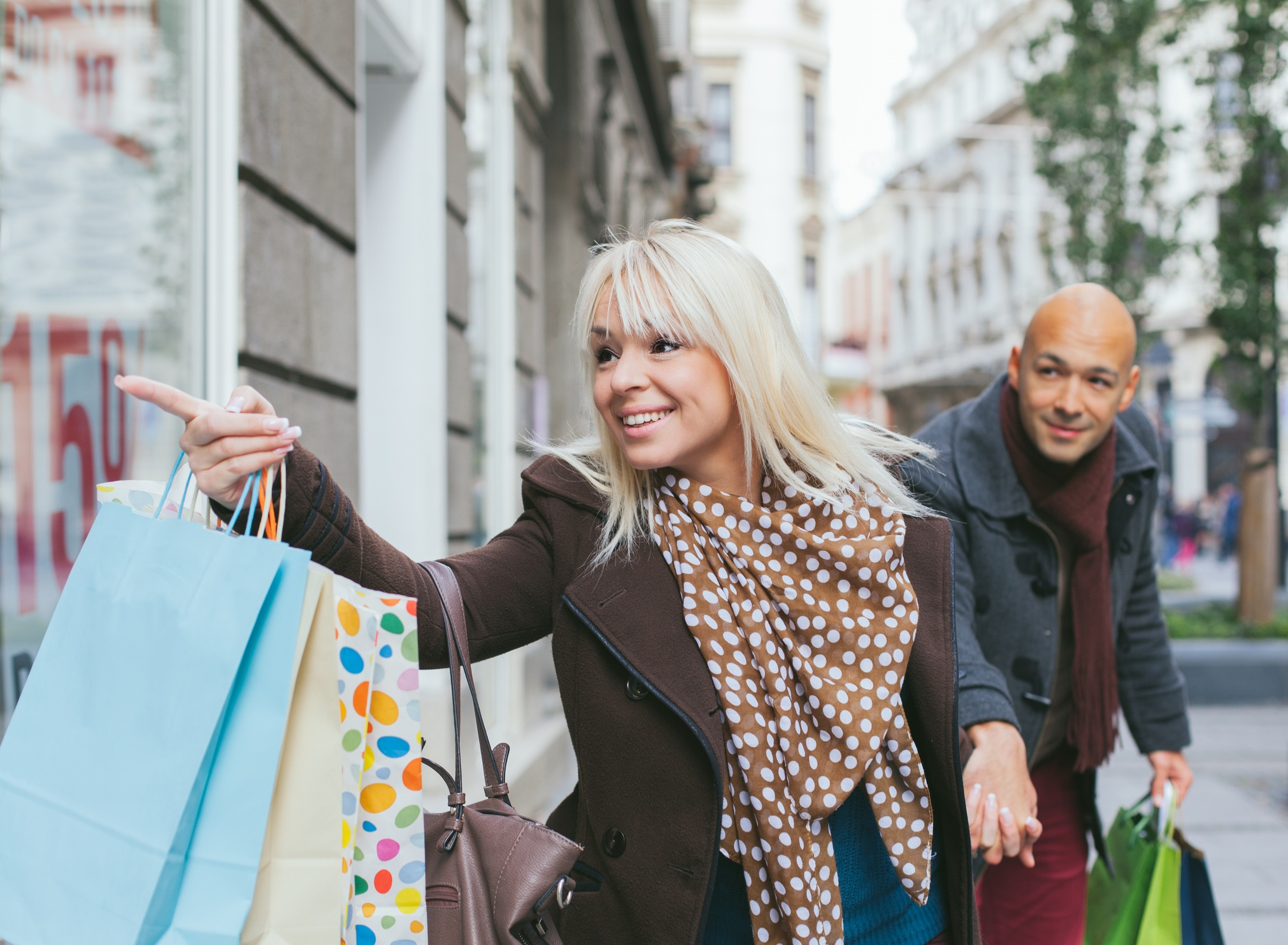 Smiling woman with shopping bags holding man's hand and pointing