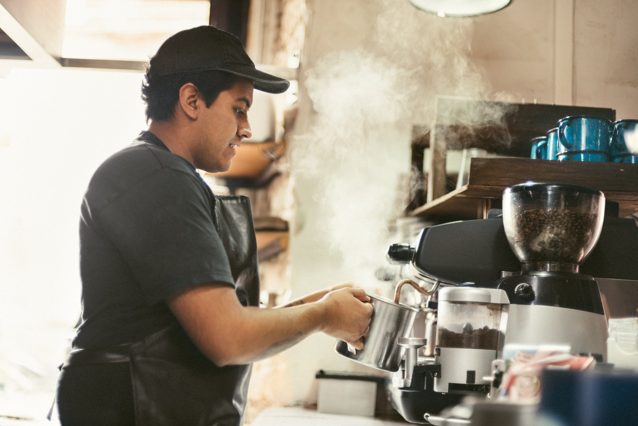 A young male barista steaming some milk.