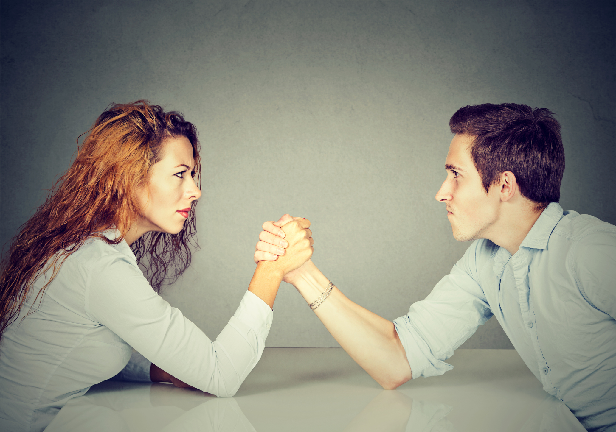 A man and woman arm wrestling.
