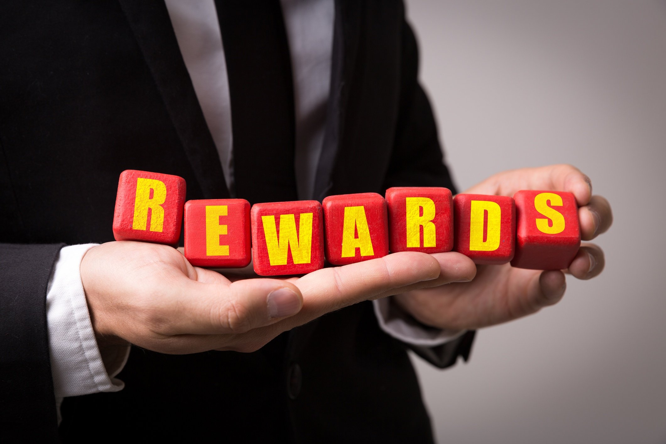 "Man in suit holding letter blocks that spell out ""rewards"""