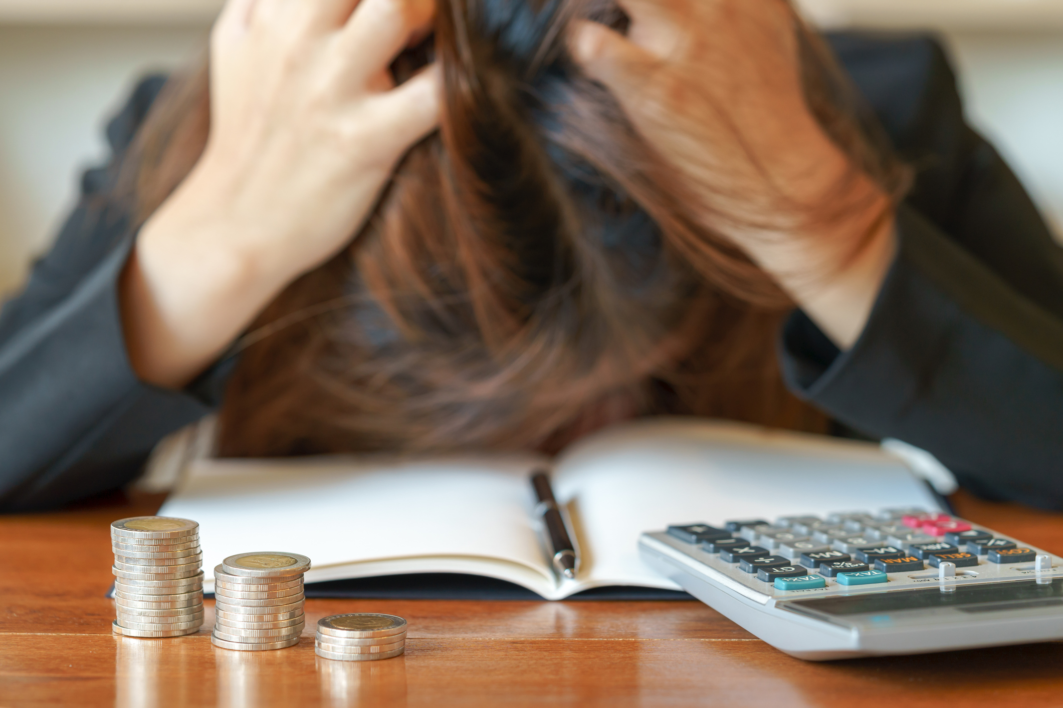Woman having a total meltdown face down on desk and clutching hair amid calculator and stacks of coins.