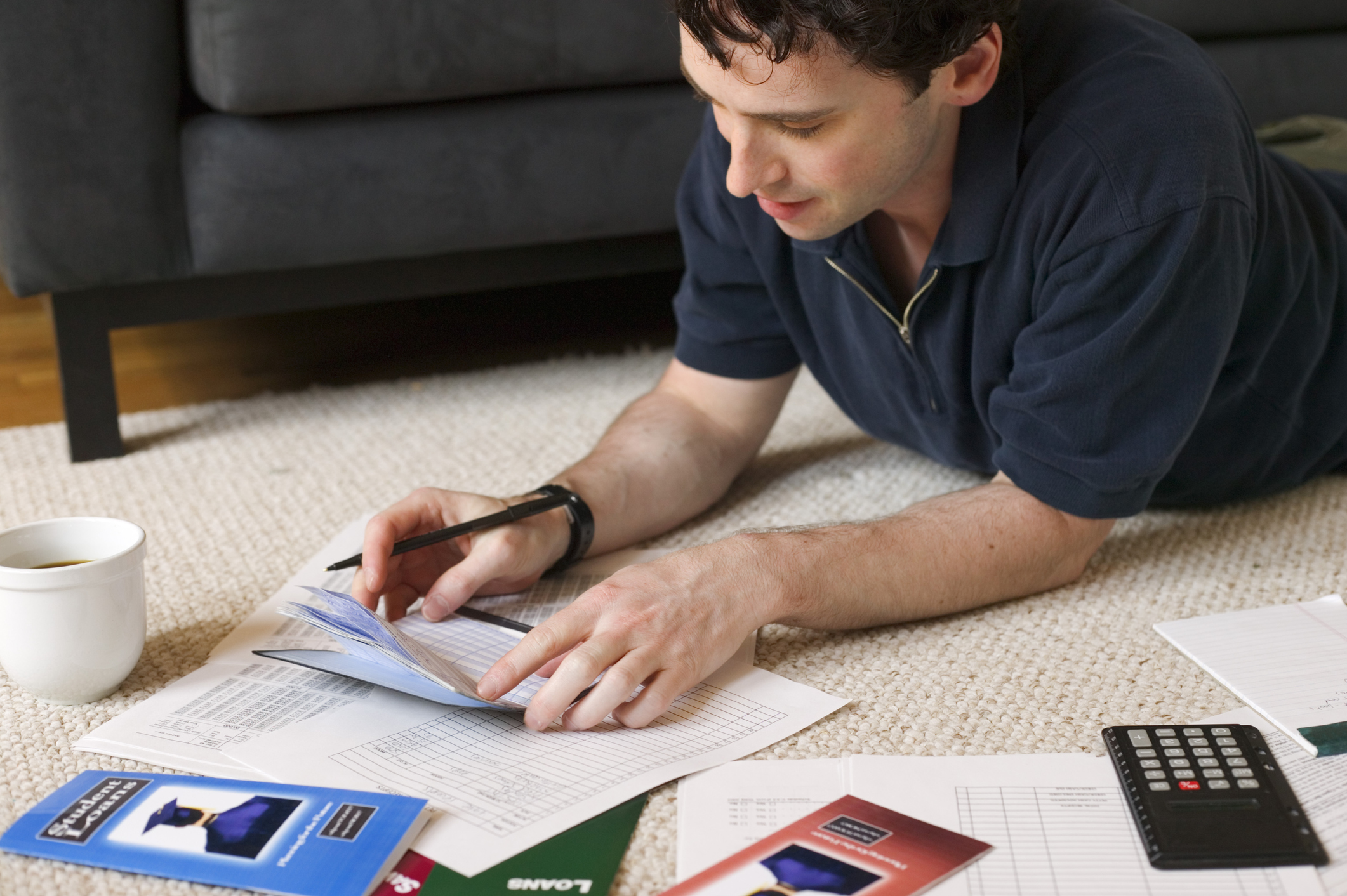 A young man making calculations in a ledger amid college brochures.