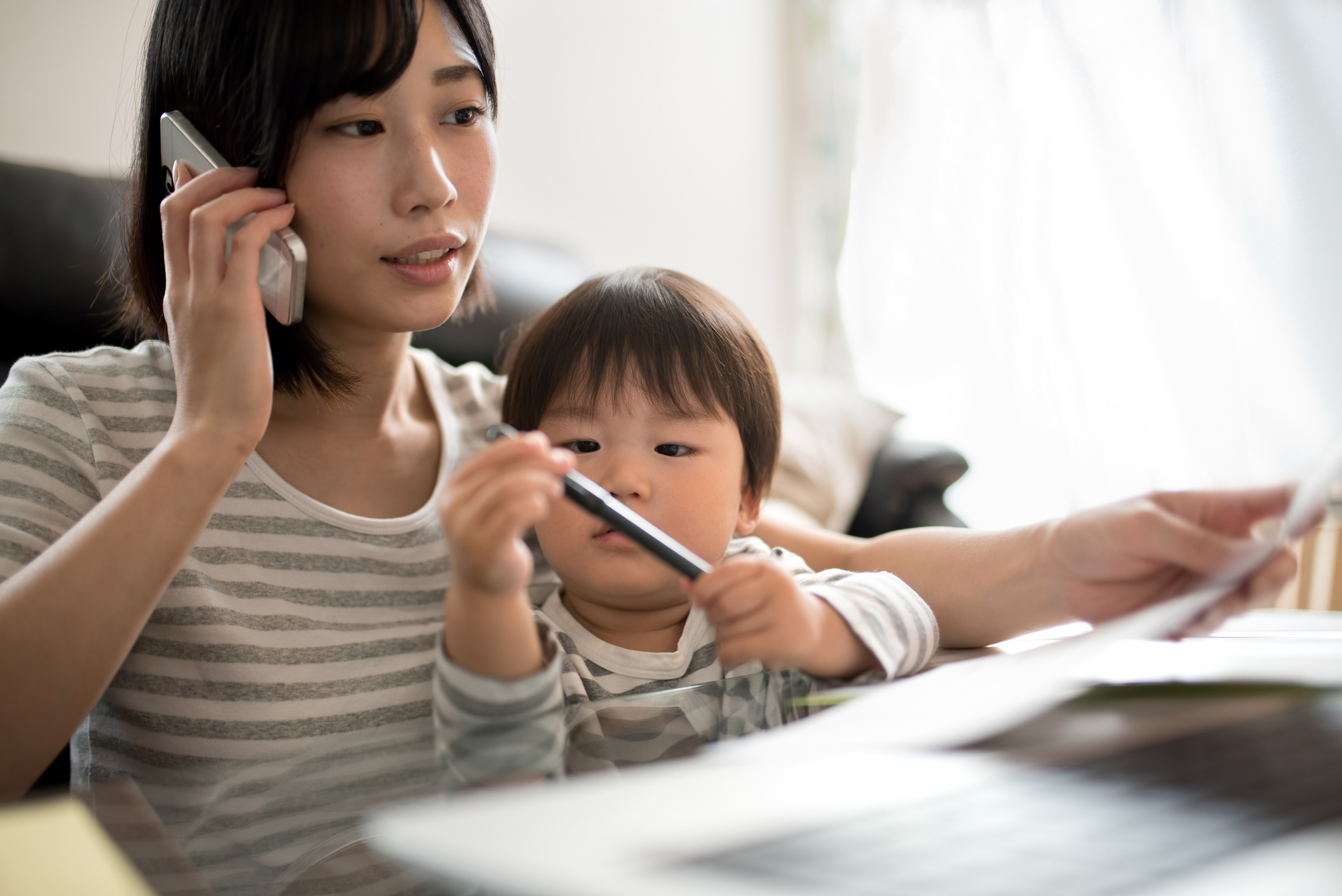 woman talking on phone while toddler sits on her lap playing with a pen.