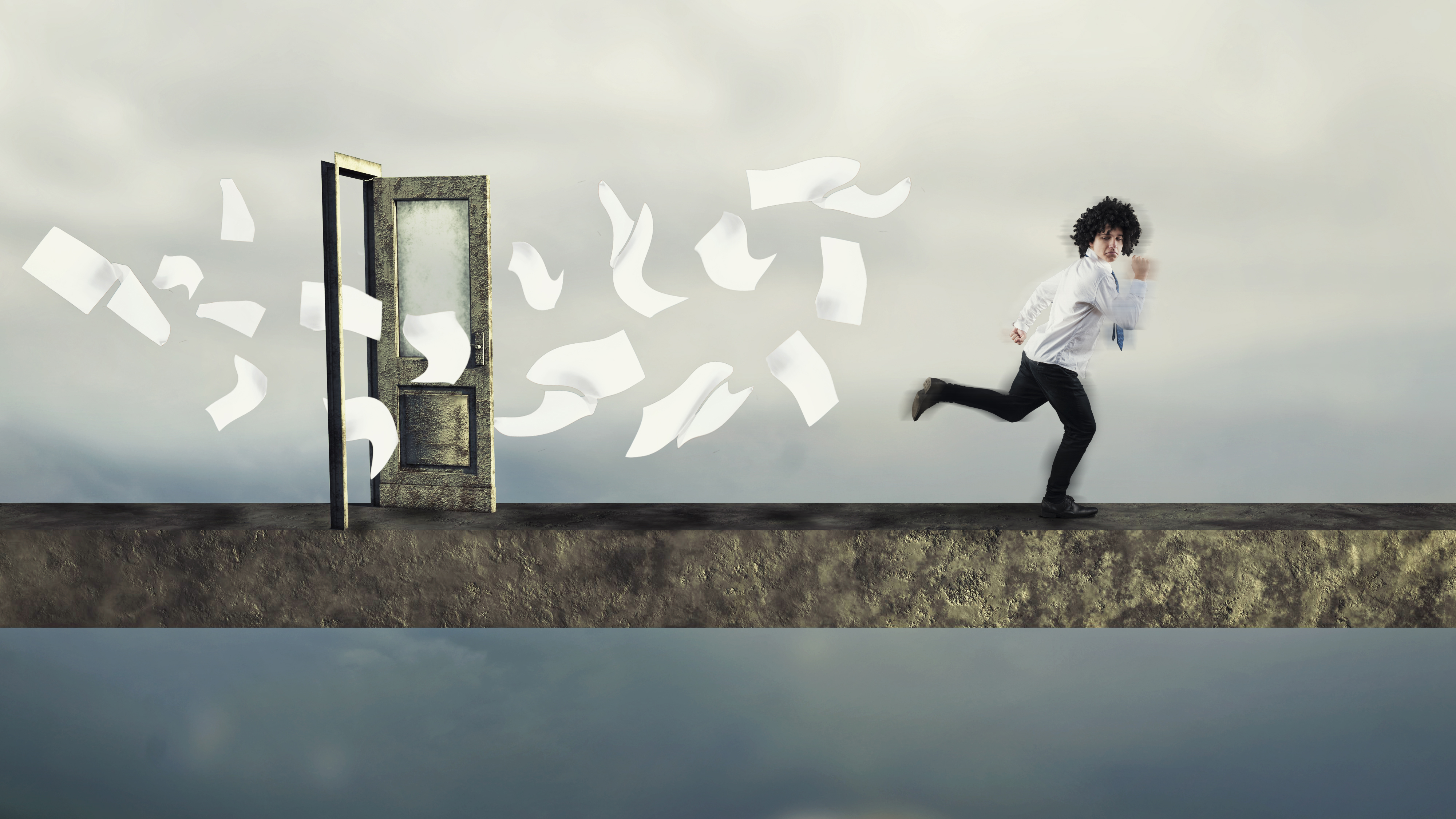 Man running through door from a whirlwind of papers.