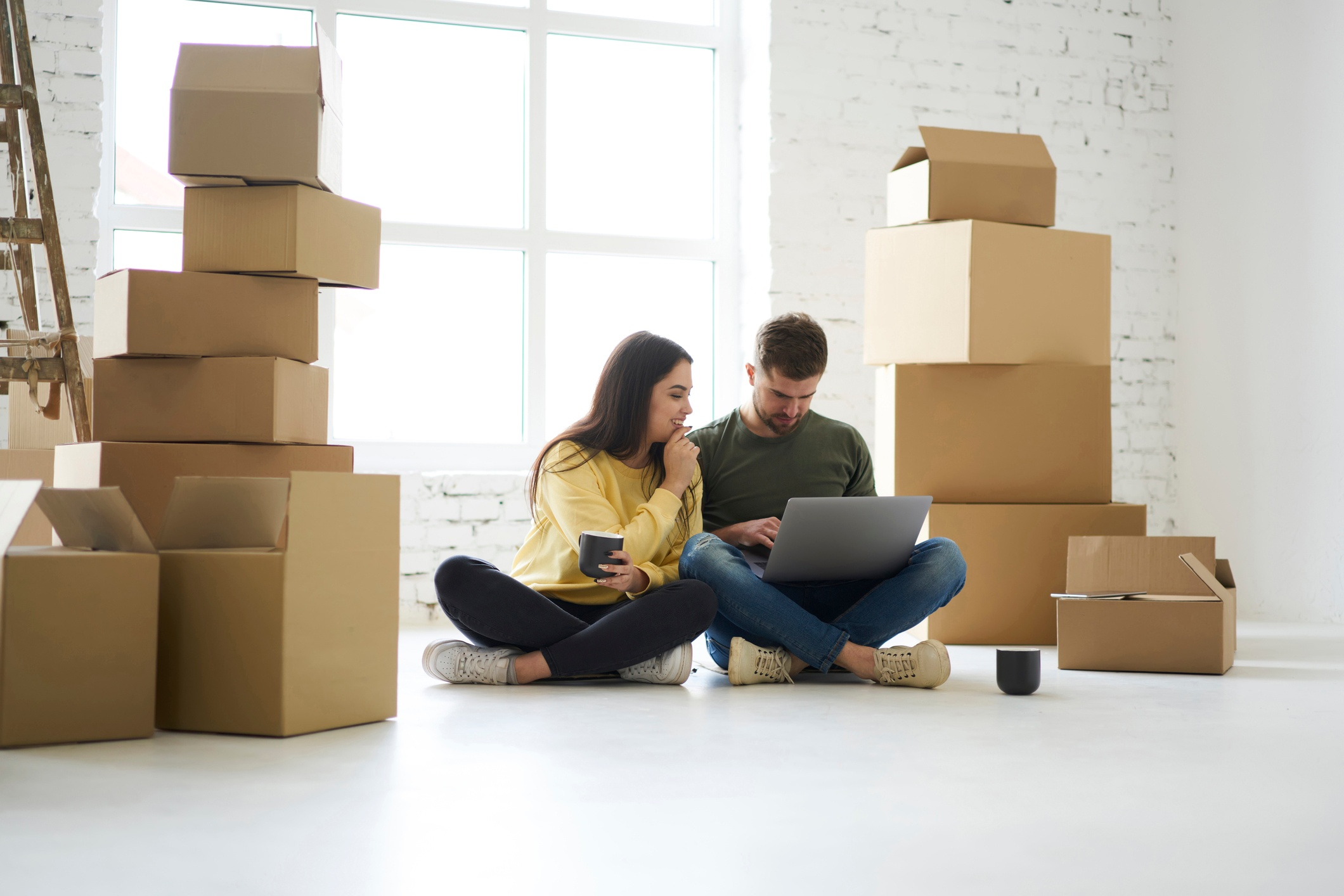 Young couple sitting on the floor of an empty apartment surrounded by cardboard boxes.