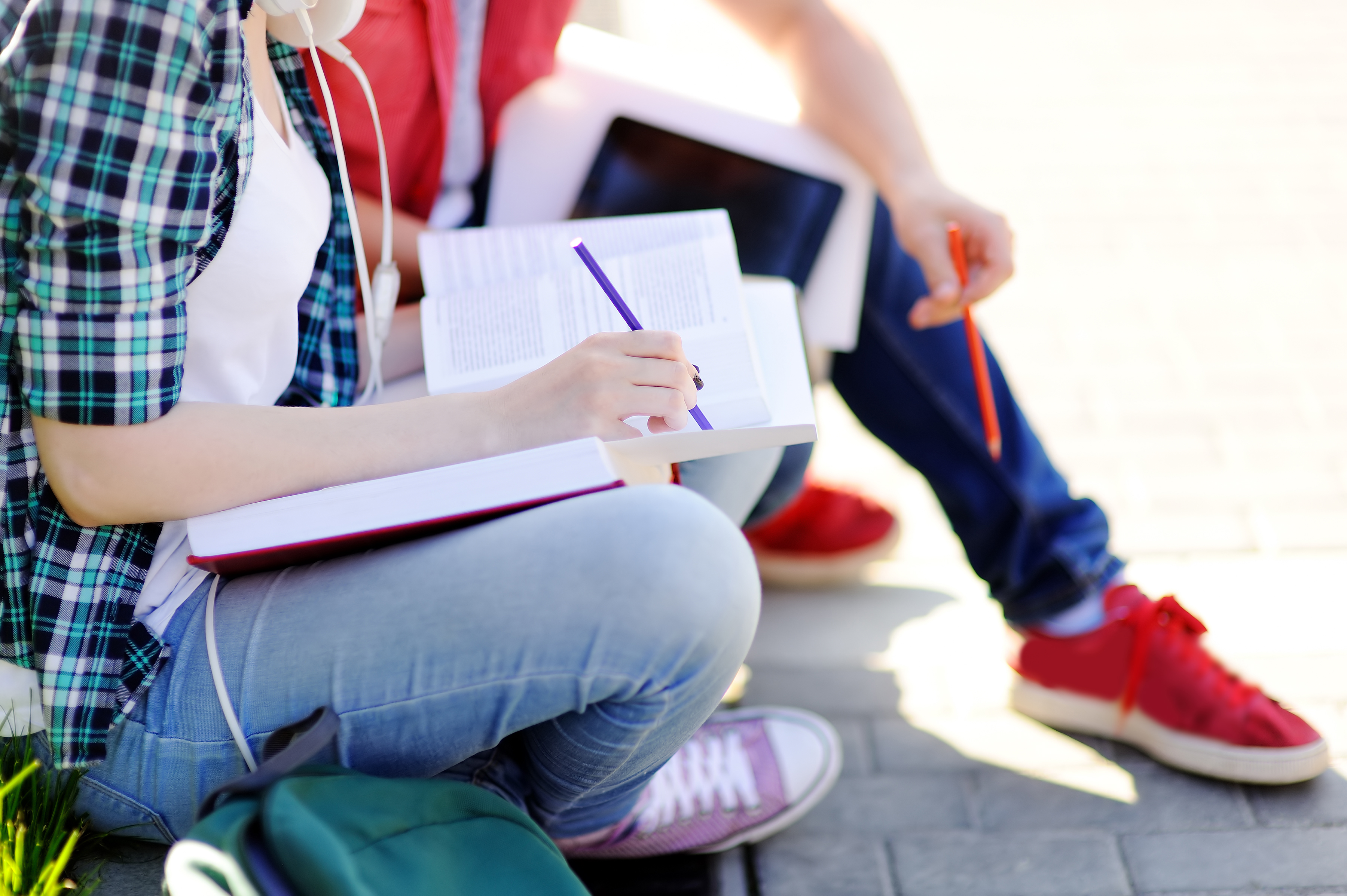 Books and pencils resting on students' knees.