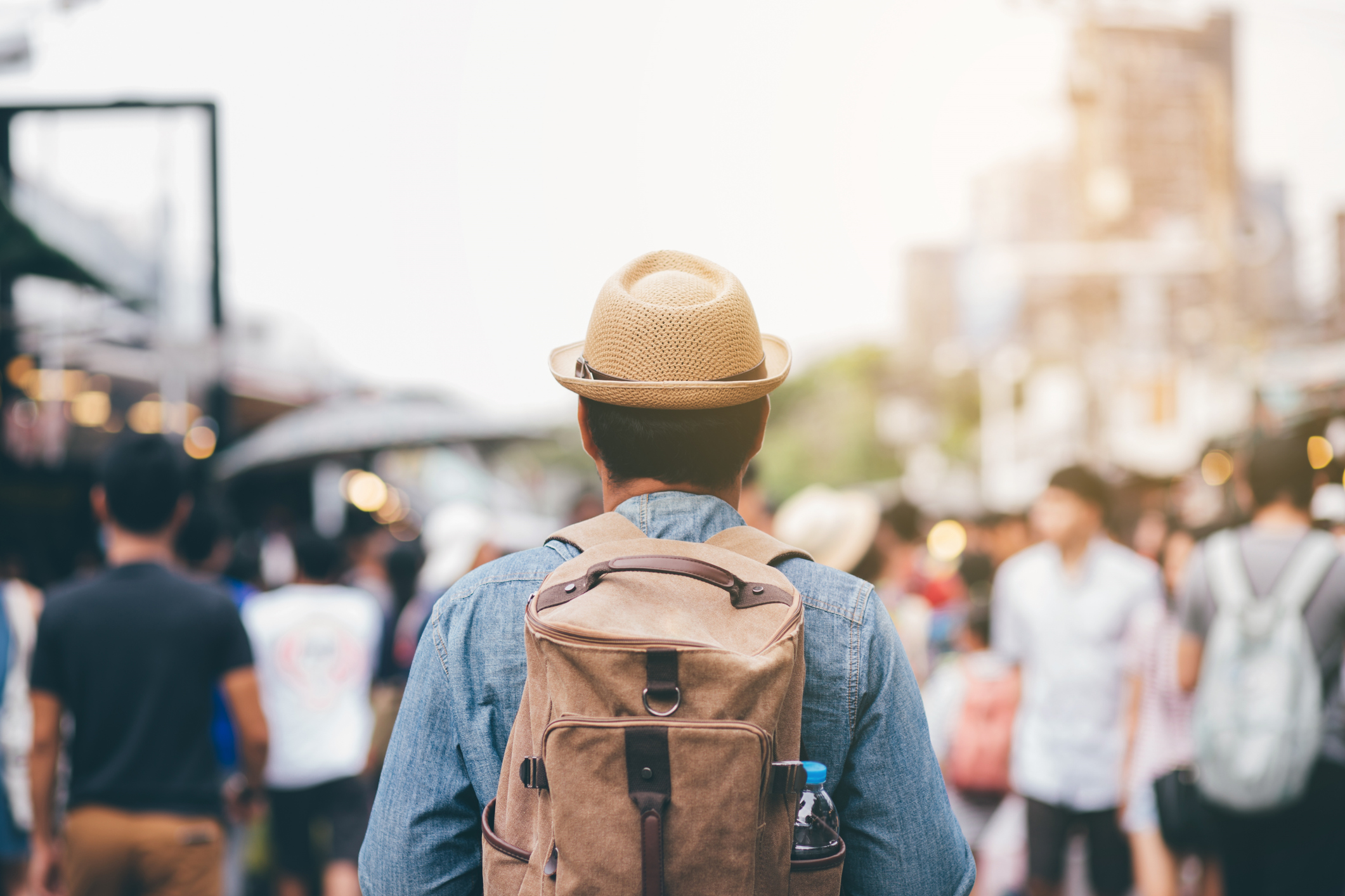 Man in backpack and straw hat facing away while walking into throng of locals in exotic locale.
