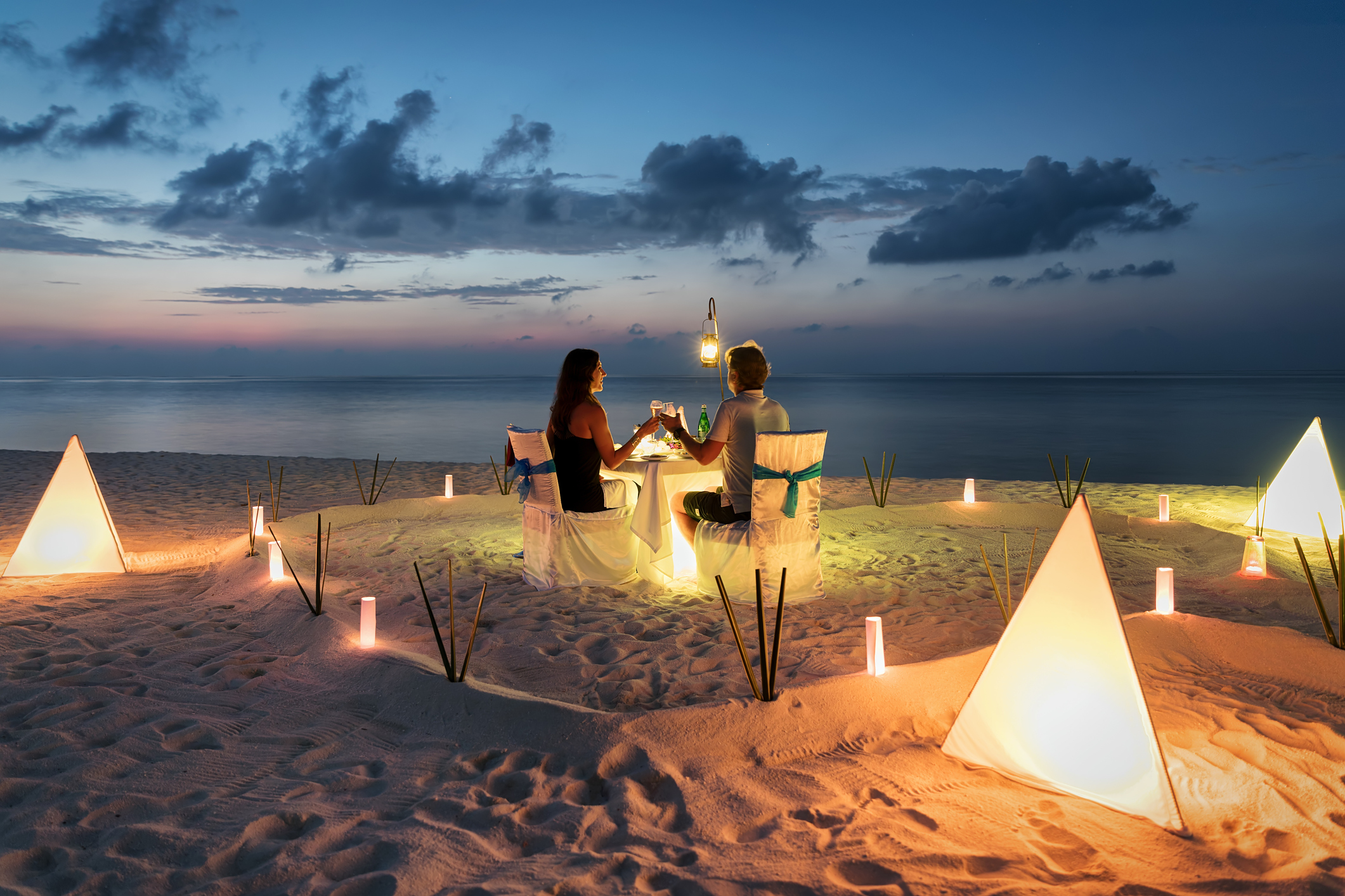 Couple toasting at an isolated restaurant-style table on the beach.