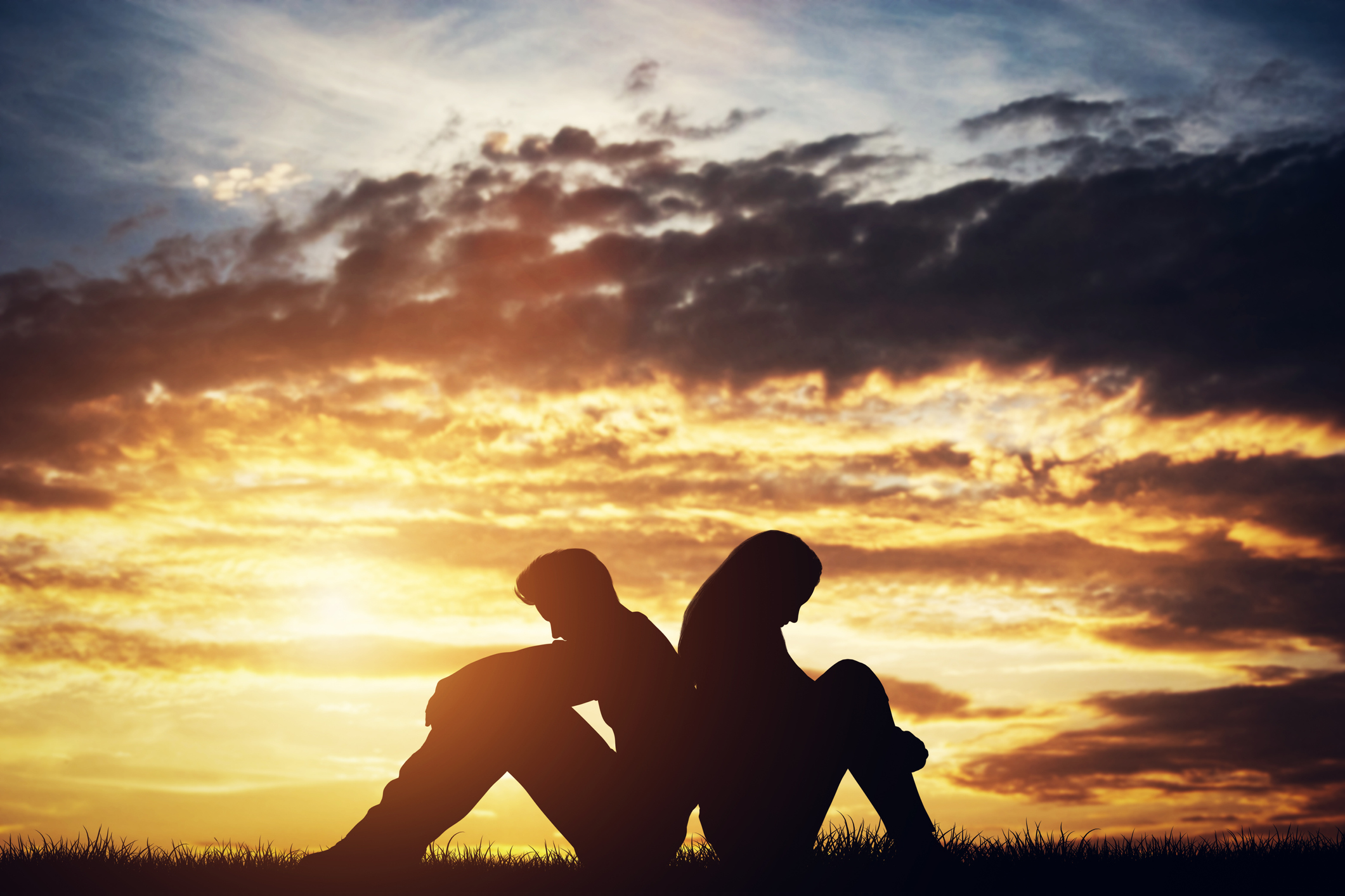 Couple in silhouette sitting back to back in an open field against a sunset.
