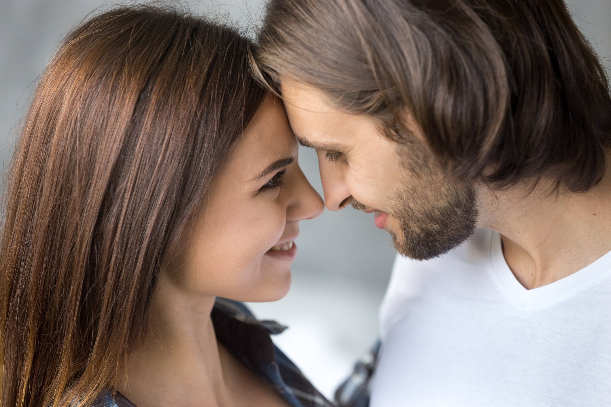 Young couple nose to nose and smiling.